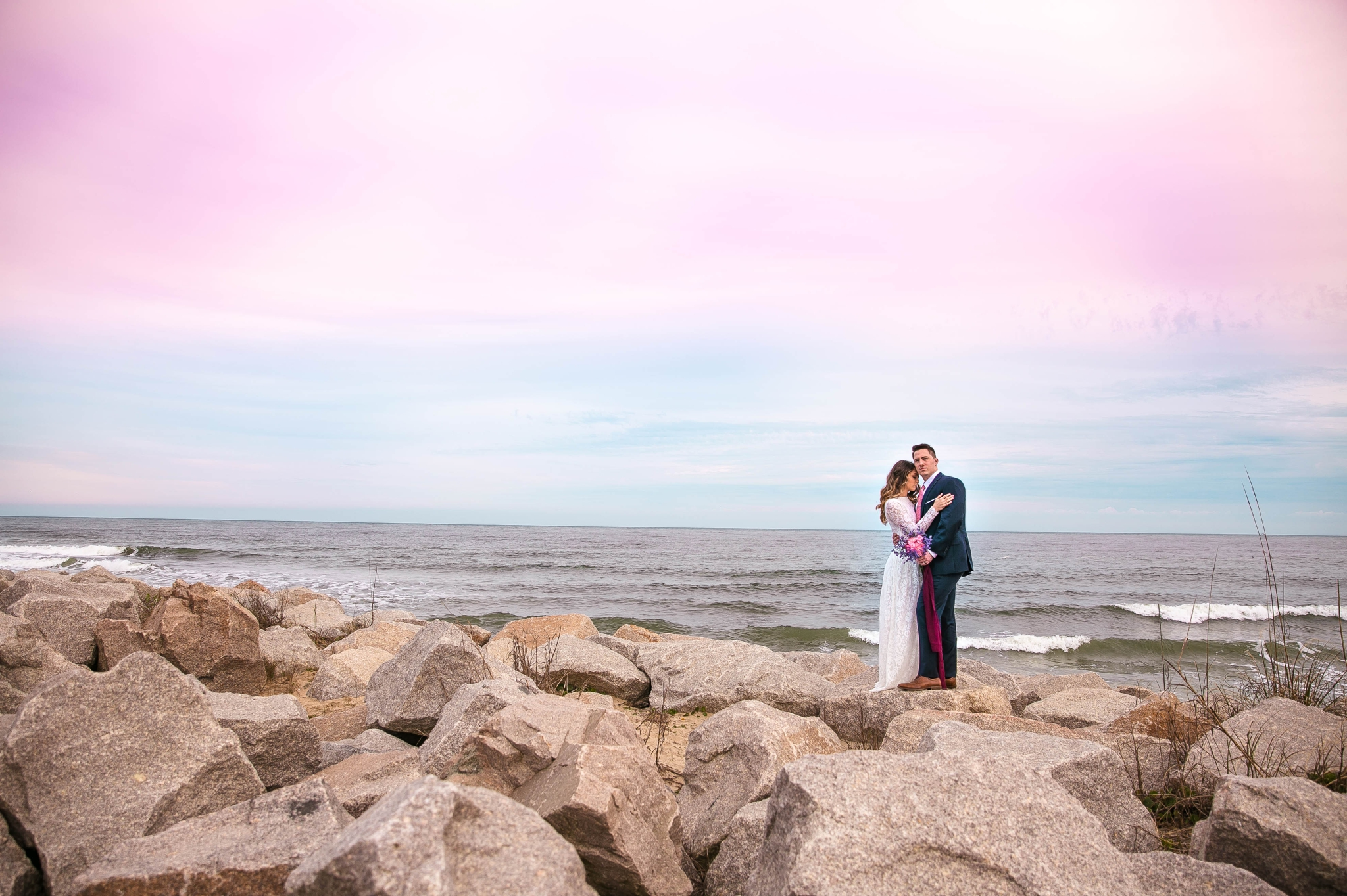 Cotton Candy Sky Beach Elopement Portraits - Bride and Groom on top of the Cliffs - - dress by asos with purple and pink flowers and navy suit - oahu hawaii wedding photographer