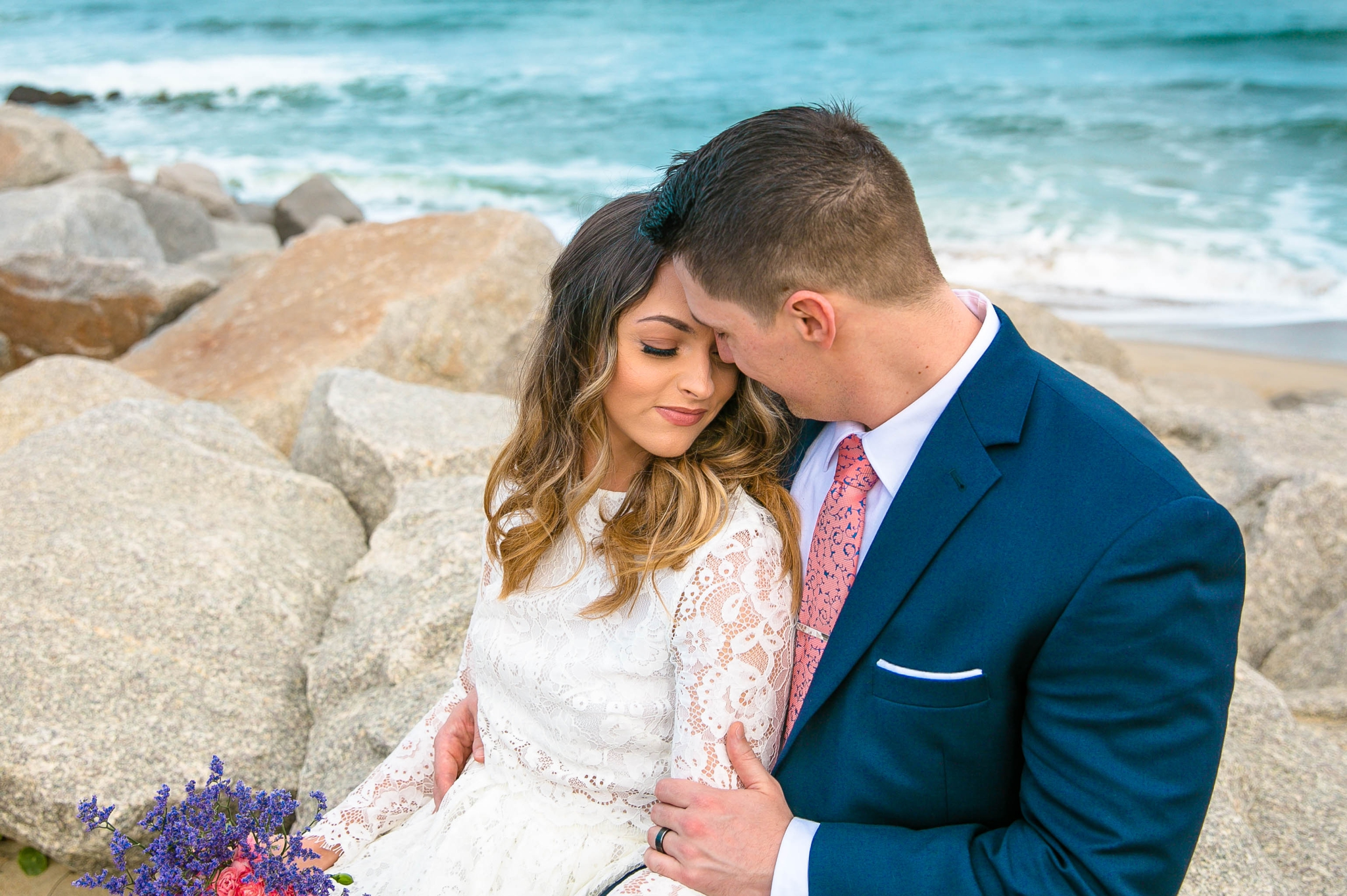 Clear blue water Beach Elopement Portraits - Bride and Groom on top of the Cliffs - - dress by asos with purple and pink flowers and navy suit - oahu hawaii wedding photographer
