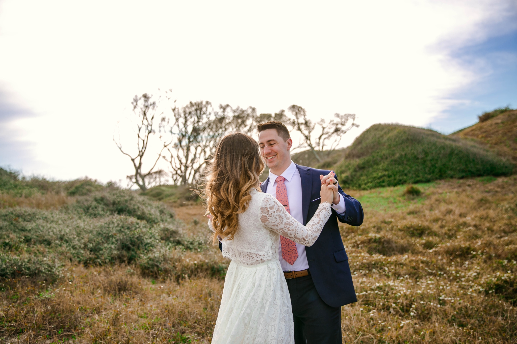 Bride and groom dancing in Lush Green Grass - Beach Elopement Photography - wedding dress by asos with purple and pink flowers and navy suit - oahu hawaii wedding photographer