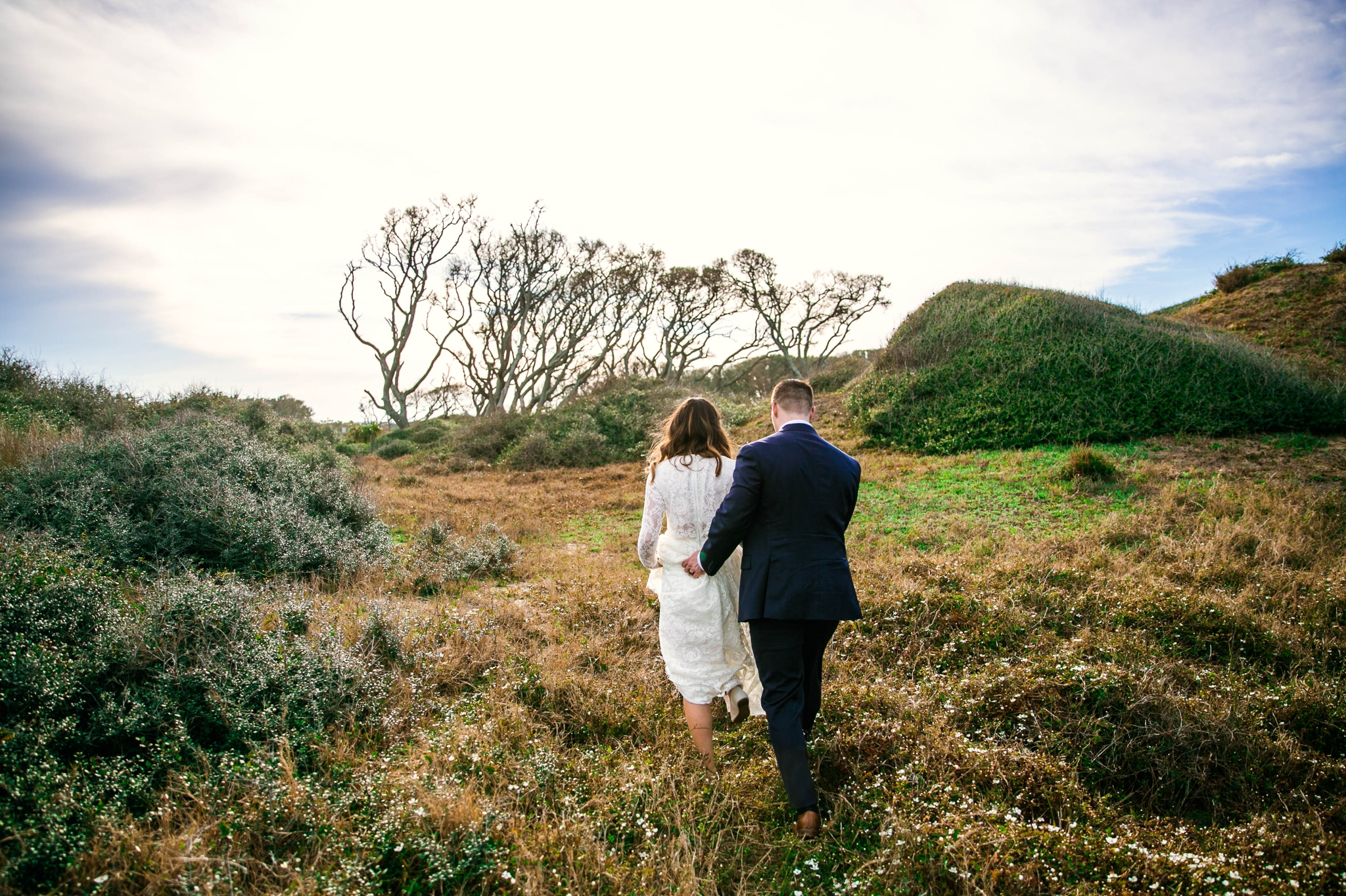 Groom holding brides dress while walking in Lush Green Hills - Beach Elopement Photography - wedding dress by asos with purple and pink flowers and navy suit - oahu hawaii wedding photographer