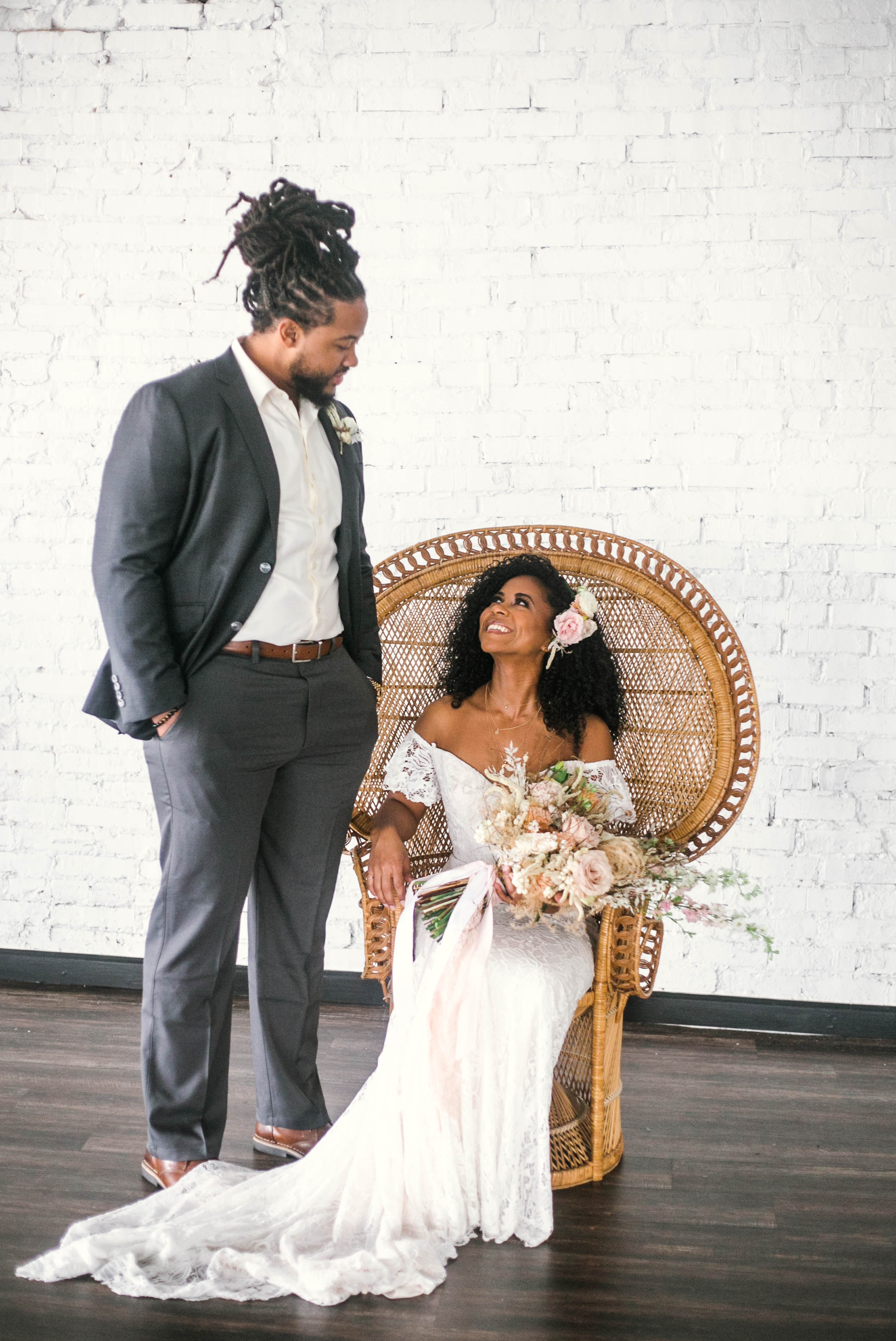 Indoor Bride and Groom Portraits, shot with natural light - black love - african american bride sitting in a Midcentury Woven Wicker Peacock Chair in a boho wedding dress with a big bouquet looking at her groom - honolulu, oahu, hawaii photographer