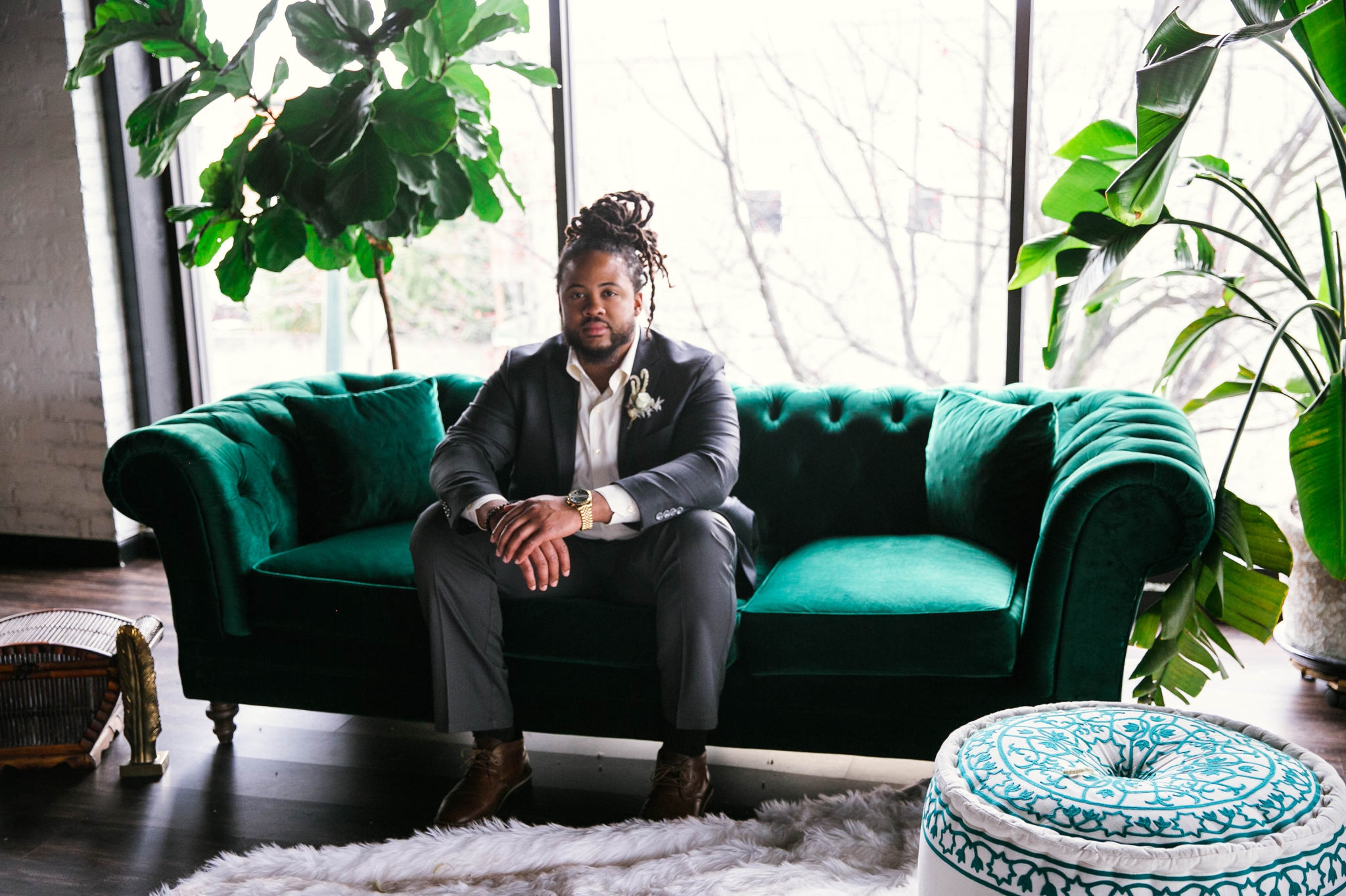 Indoor Natural light portrait of a black groom sitting on an emerald tufted sofa - laughing and having fun with each other- flowers in natural african american hair - oahu hawaii wedding photographer