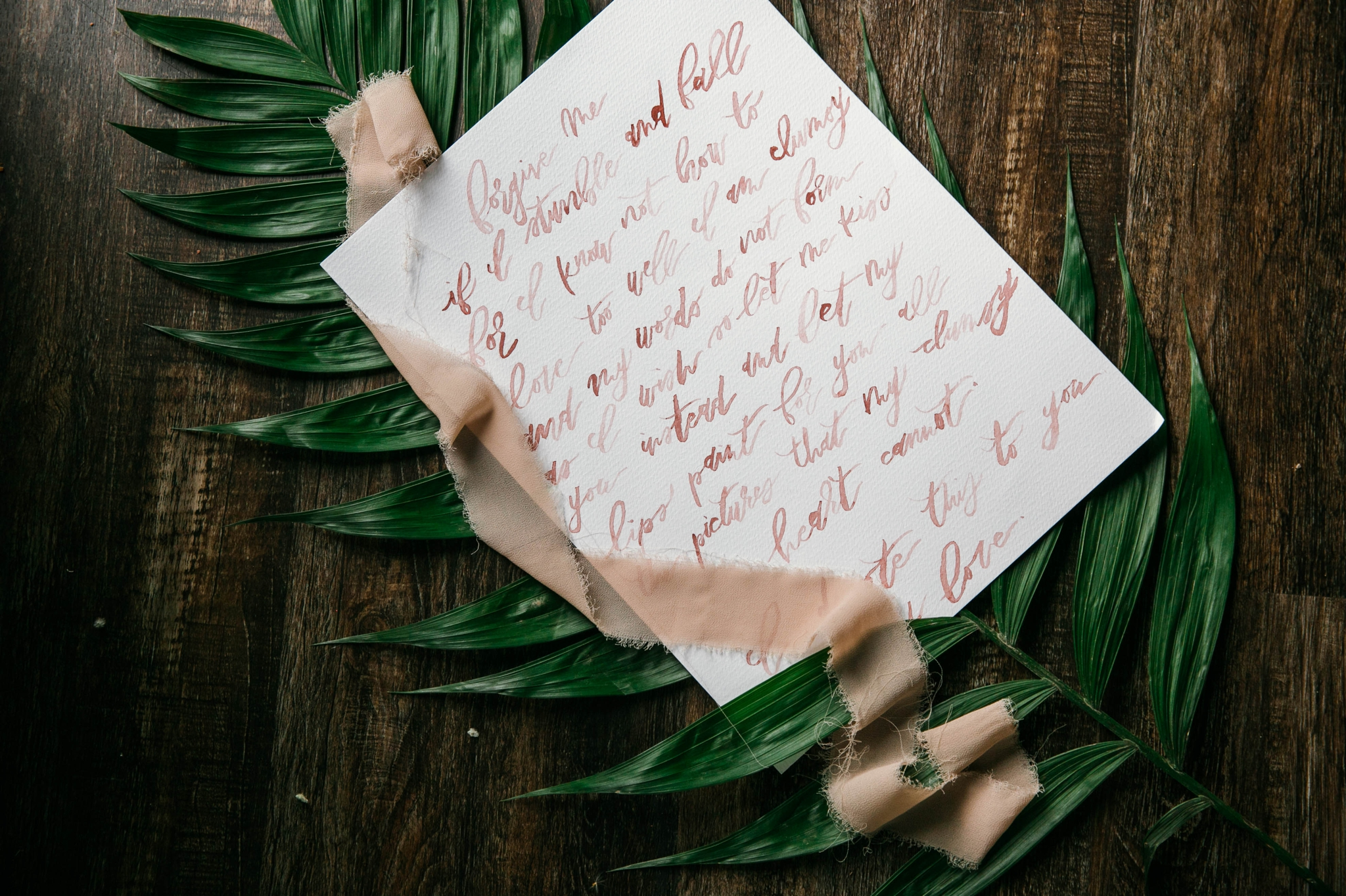 Lay flat of Wedding Vows with a tropical leave as the background with light pink ribbon styled by Johanna Dye Photography designed by Tortoise.Design - Oahu Hawaii Wedding Photographer