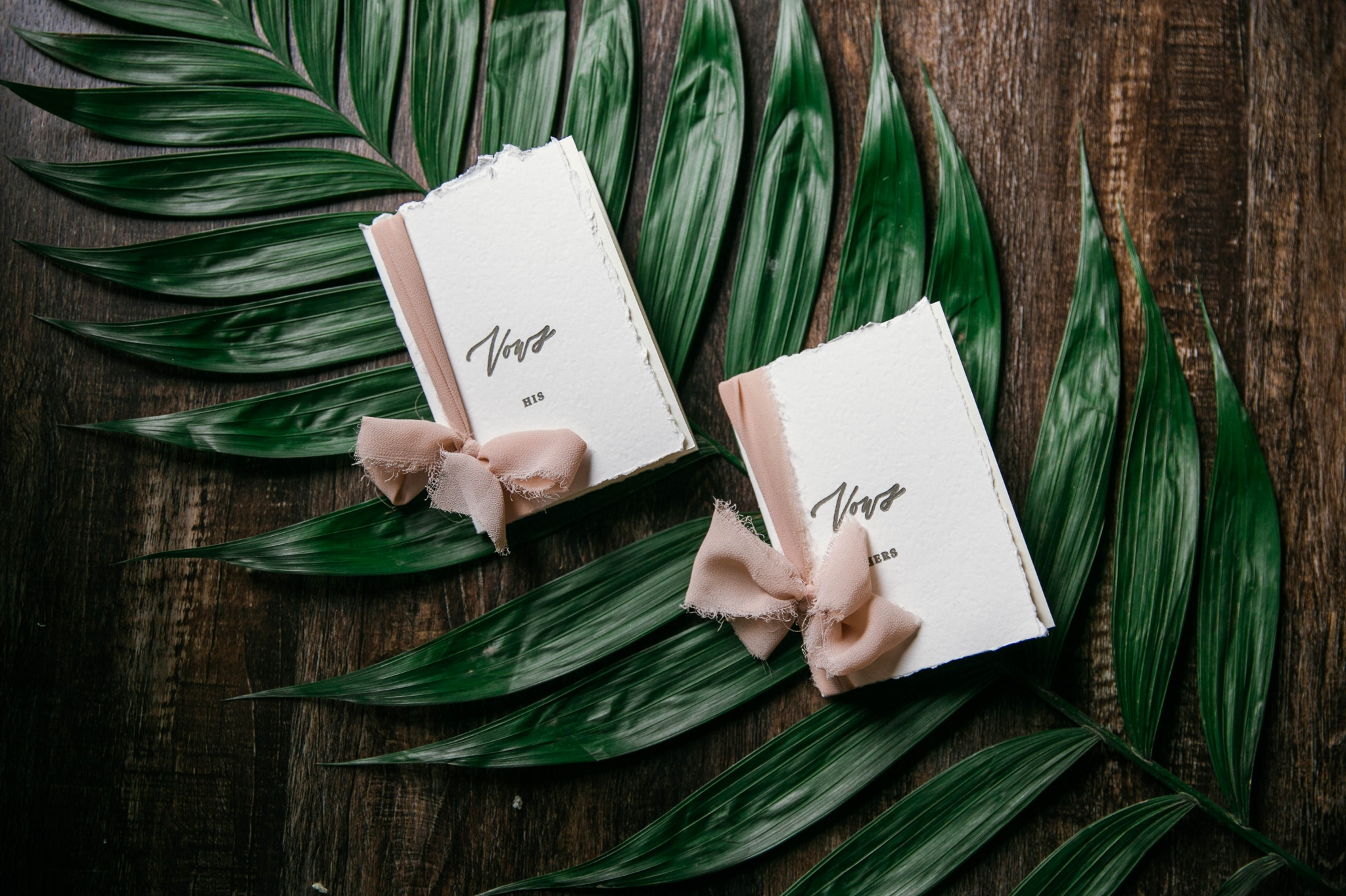 Lay flat of Wedding Vow books with a tropical leave as the background with light pink ribbon styled by Johanna Dye Photography designed by Tortoise.Design - Tropical Destination Wedding Inspiration - Oahu Hawaii Wedding Photographer
