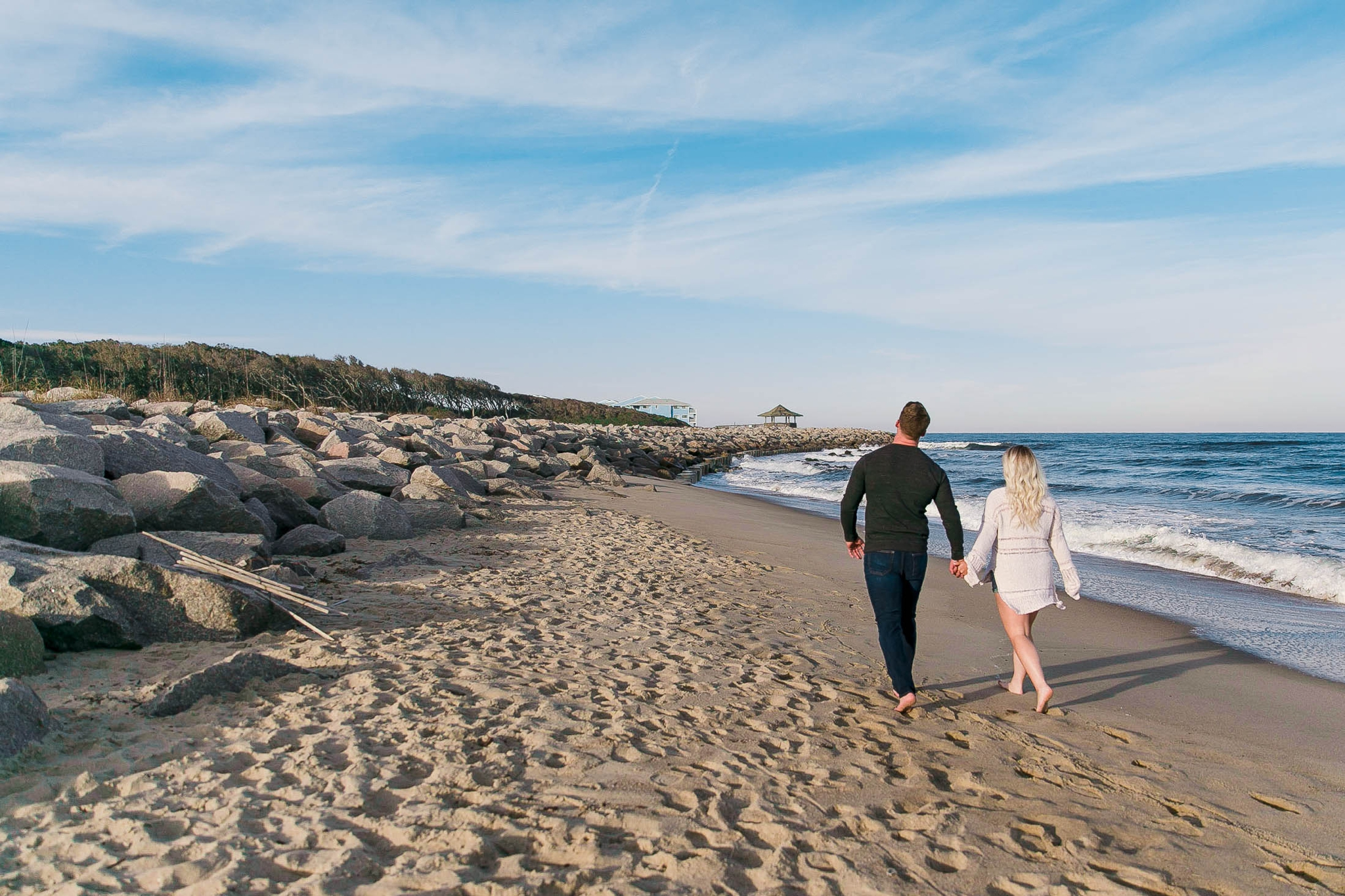 couple walking on the beach on a sunny day - girl wearing ripped jeans shorts and a white free people sweater - Casual Beach Engagement Photography Session - Honolulu Oahu Hawaii Wedding Photographer - Johanna Dye