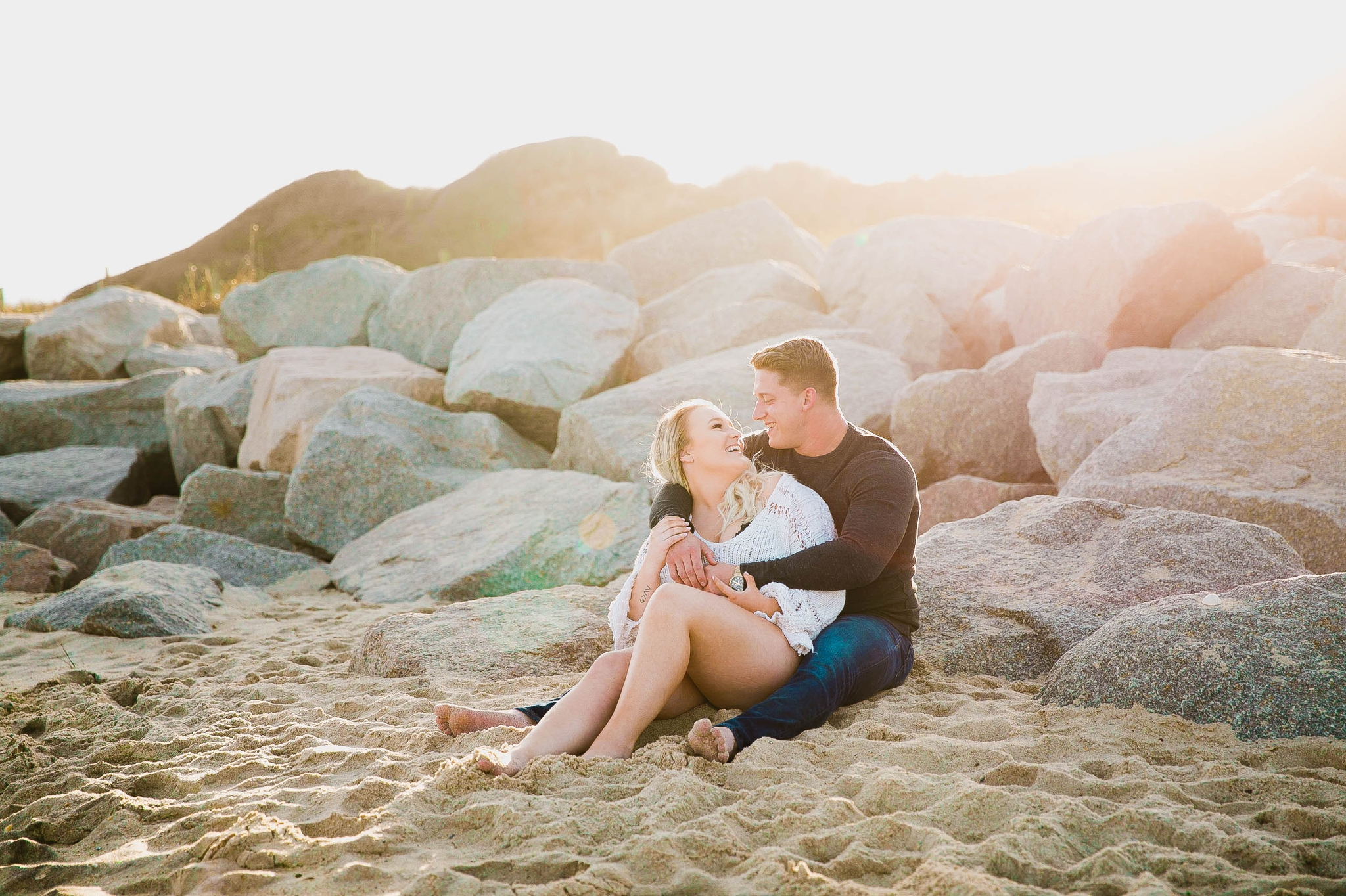 couple looking at the ocean while sitting on a sandy beach at sunset with golden hour light shining onto them - girl wearing ripped jeans shorts and a white free people sweater - Casual Beach Engagement Photography Session - Honolulu Oahu Hawaii Wedding Photographer - Johanna Dye