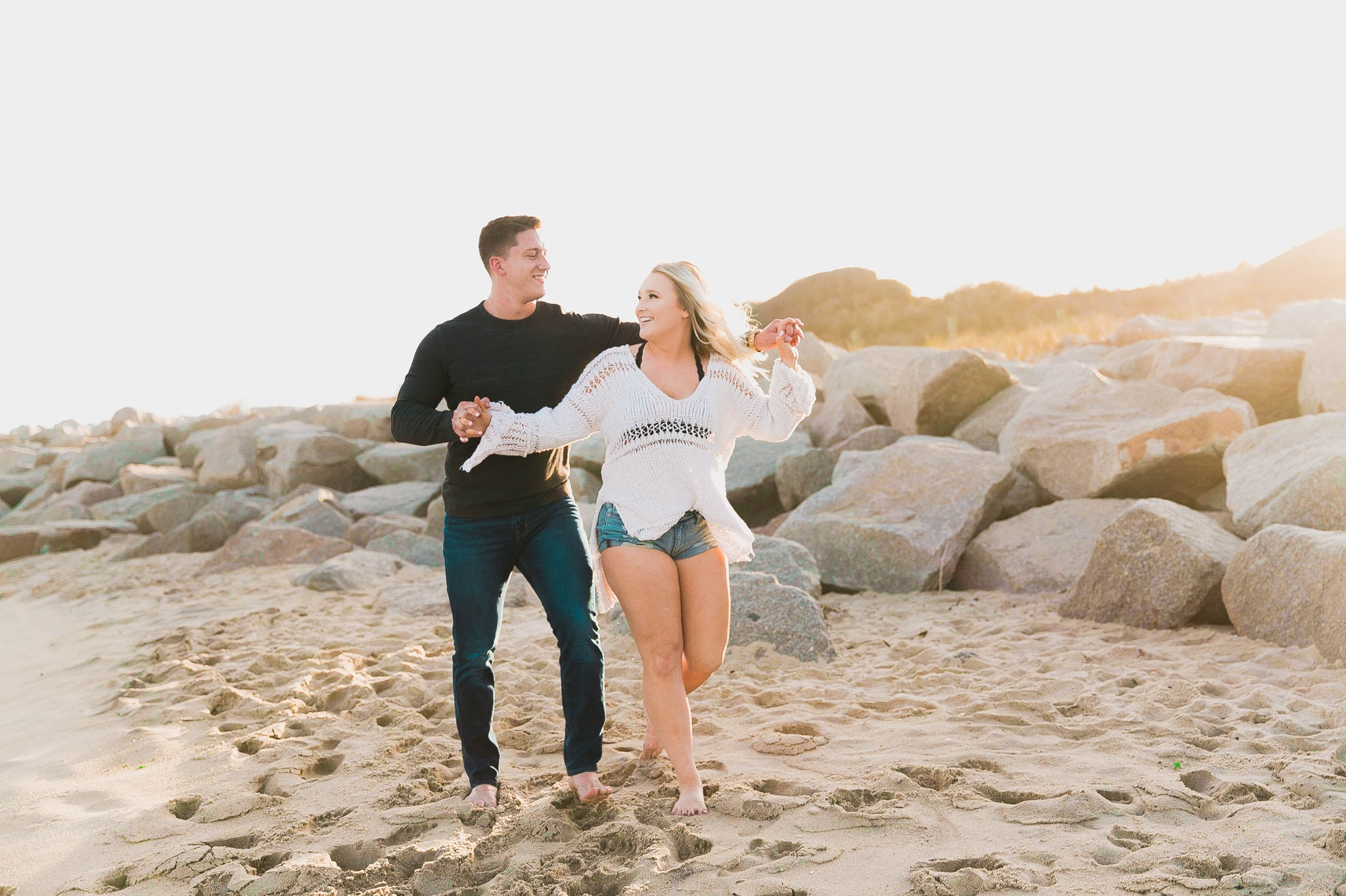couple being playful at the beach and doing the titanic flying pose at sunset during golden hour light - girl wearing ripped jeans shorts and a white free people sweater - Casual Beach Engagement Photography Session - Honolulu Oahu Hawaii Wedding Photographer - Johanna Dye