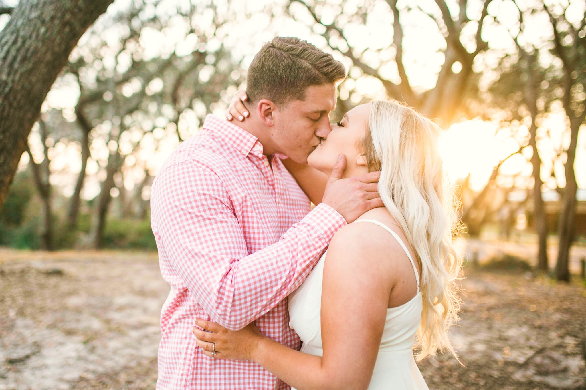 Engagement Photography Session beneath tropical trees at sunset during golden hour light -  man kissing his fiance - girl is wearing a white flowy maxi dress from lulus - Honolulu Oahu Hawaii Wedding Photographer - Johanna Dye