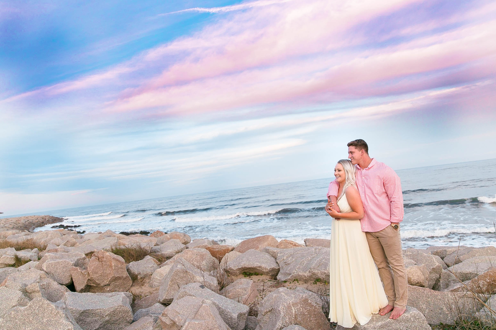 Engagement Photography Session at the beach on top of rocks with a cotton candy sky in the background - couple is kissing - girl is wearing a white flowy maxi dress from lulus - Honolulu Oahu Hawaii Wedding Photographer - Johanna Dye