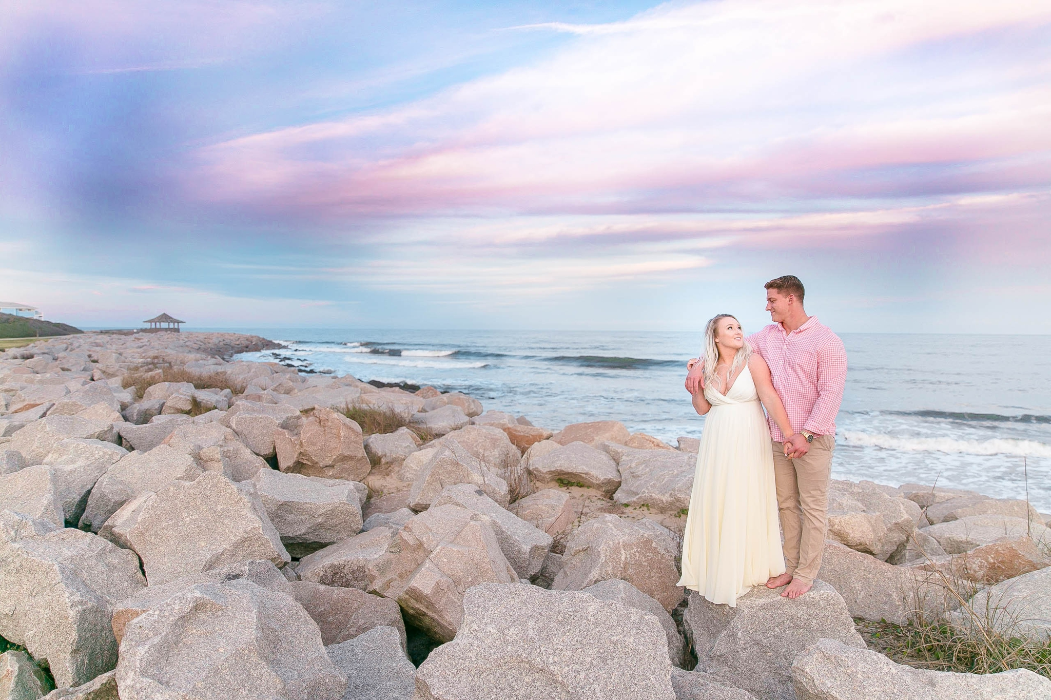 Engagement Photography Session at the beach on top of rocks with a cotton candy sky in the background - couple is standing up - girl is wearing a white flowy maxi dress from lulus - Honolulu Oahu Hawaii Wedding Photographer - Johanna Dye