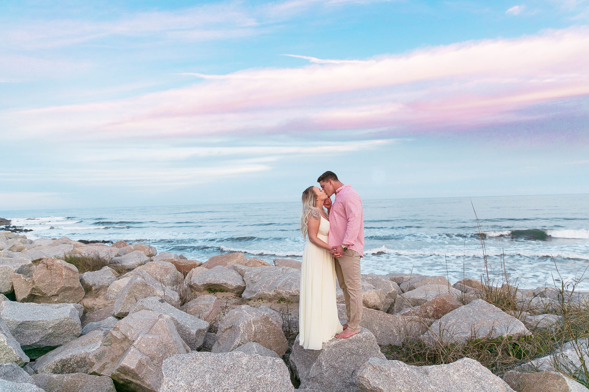 Engagement Photography Session at the beach on top of rocks with a cotton candy sky in the background - couple is looking at each other - girl is wearing a white flowy maxi dress from lulus - Honolulu Oahu Hawaii Wedding Photographer - Johanna Dye