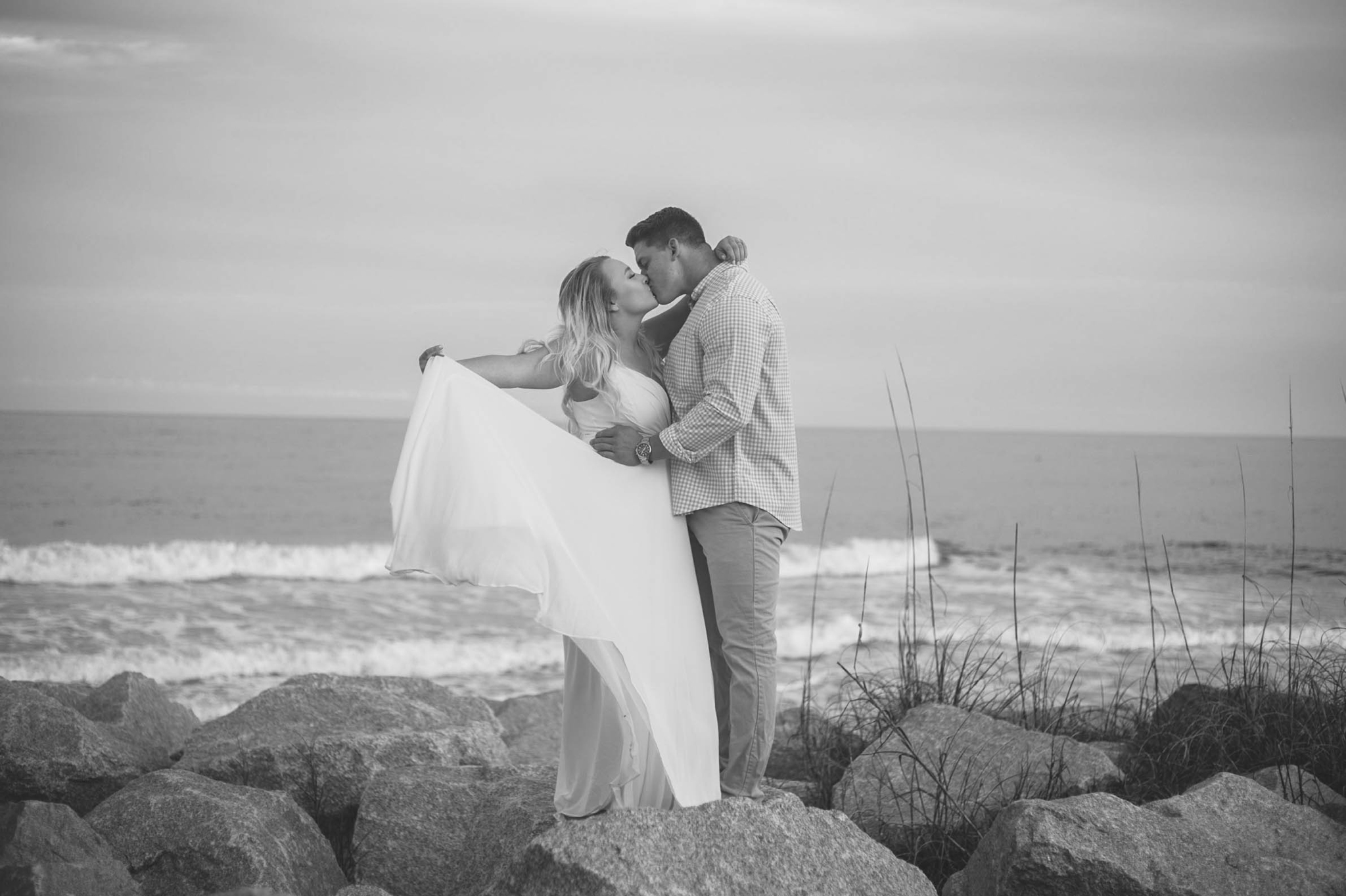 Black and White Engagement Photography Session at the beach on top of rocks  - couple is kissing - girl is wearing a white flowy maxi dress from lulus - Honolulu Oahu Hawaii Wedding Photographer - Johanna Dye