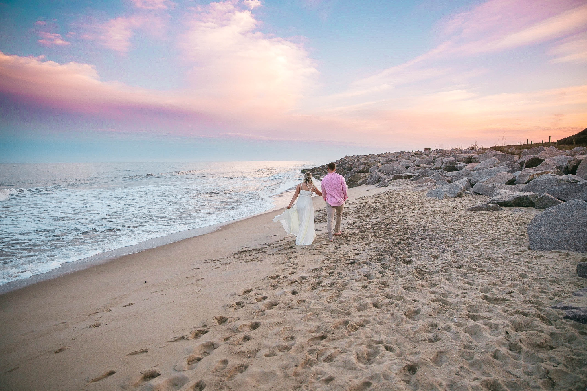 Romantic Engagement Photography Session at the beach during sunset with a cotton candy sky - couple is walking in the sand - girl is wearing a white flowy maxi dress from lulus - Honolulu Oahu Hawaii Wedding Photographer - Johanna Dye
