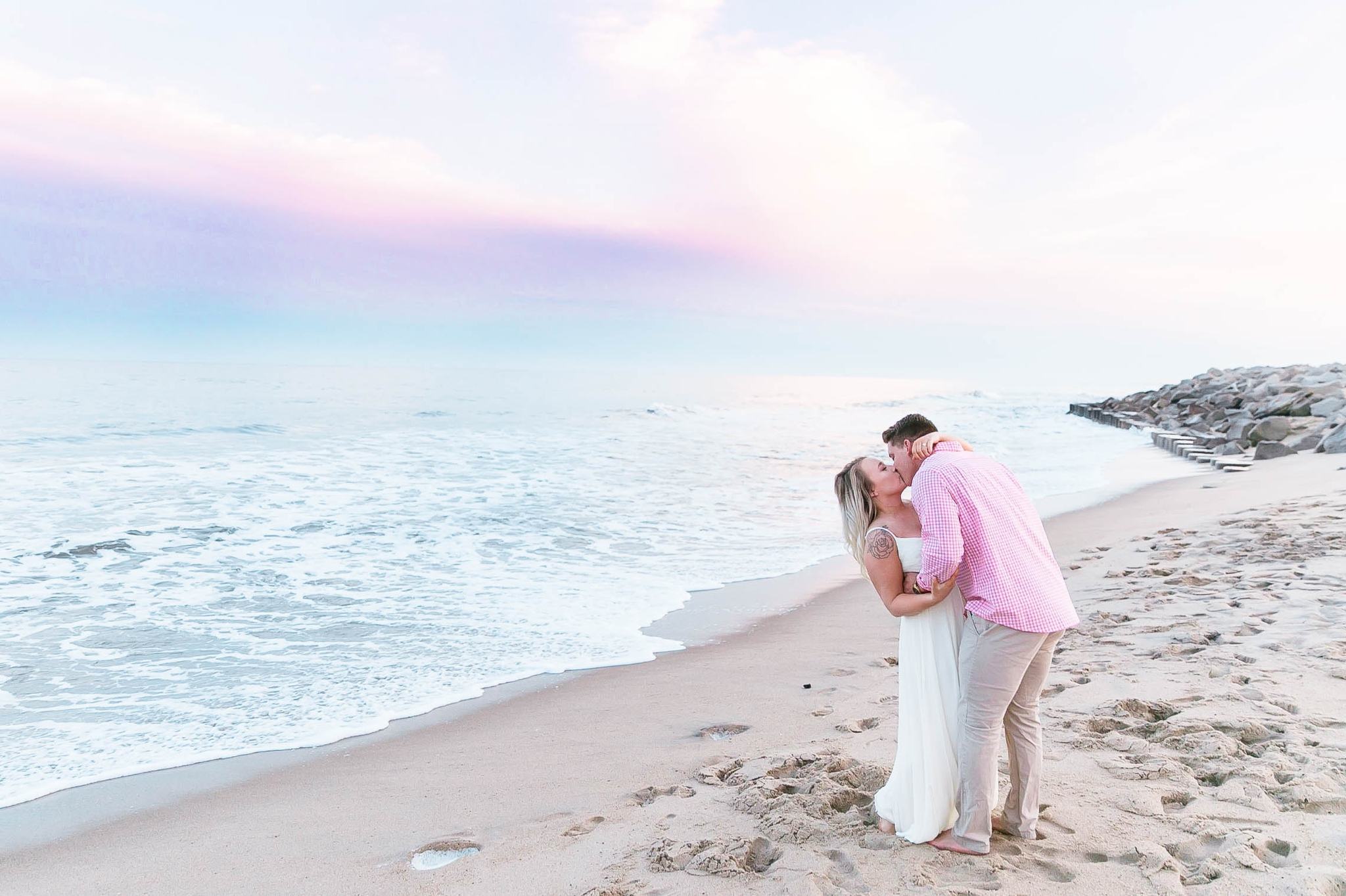 Romantic Engagement Photography Session at the beach during sunset with a cotton candy sky - guy is kissing his fiance - girl is wearing a white flowy maxi dress from lulus - Honolulu Oahu Hawaii Wedding Photographer - Johanna Dye