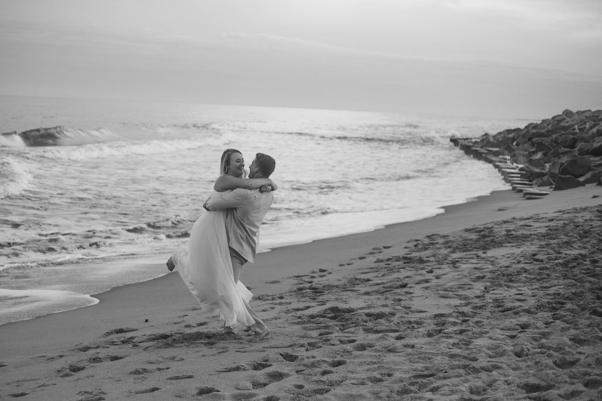 Black and White Romantic Engagement Photography Session at the beach during sunset - guy is kissing his fiance - girl is wearing a white flowy maxi dress from lulus - Honolulu Oahu Hawaii Wedding Photographer - Johanna Dye