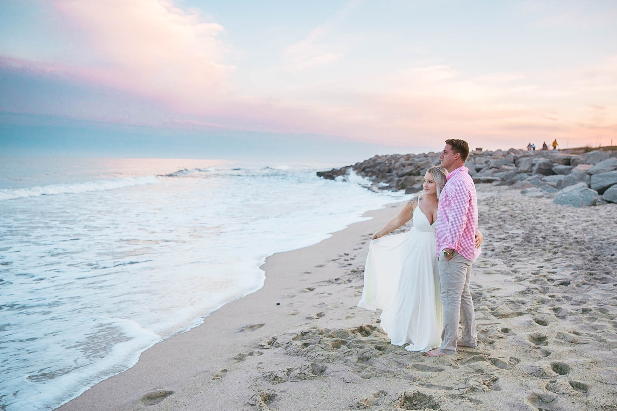 Romantic Engagement Photography Session at the beach during sunset with a cotton candy sky - couple is looking at the ocean while standing in the sand - girl is wearing a white flowy maxi dress from lulus - Honolulu Oahu Hawaii Wedding Photographer - Johanna Dye
