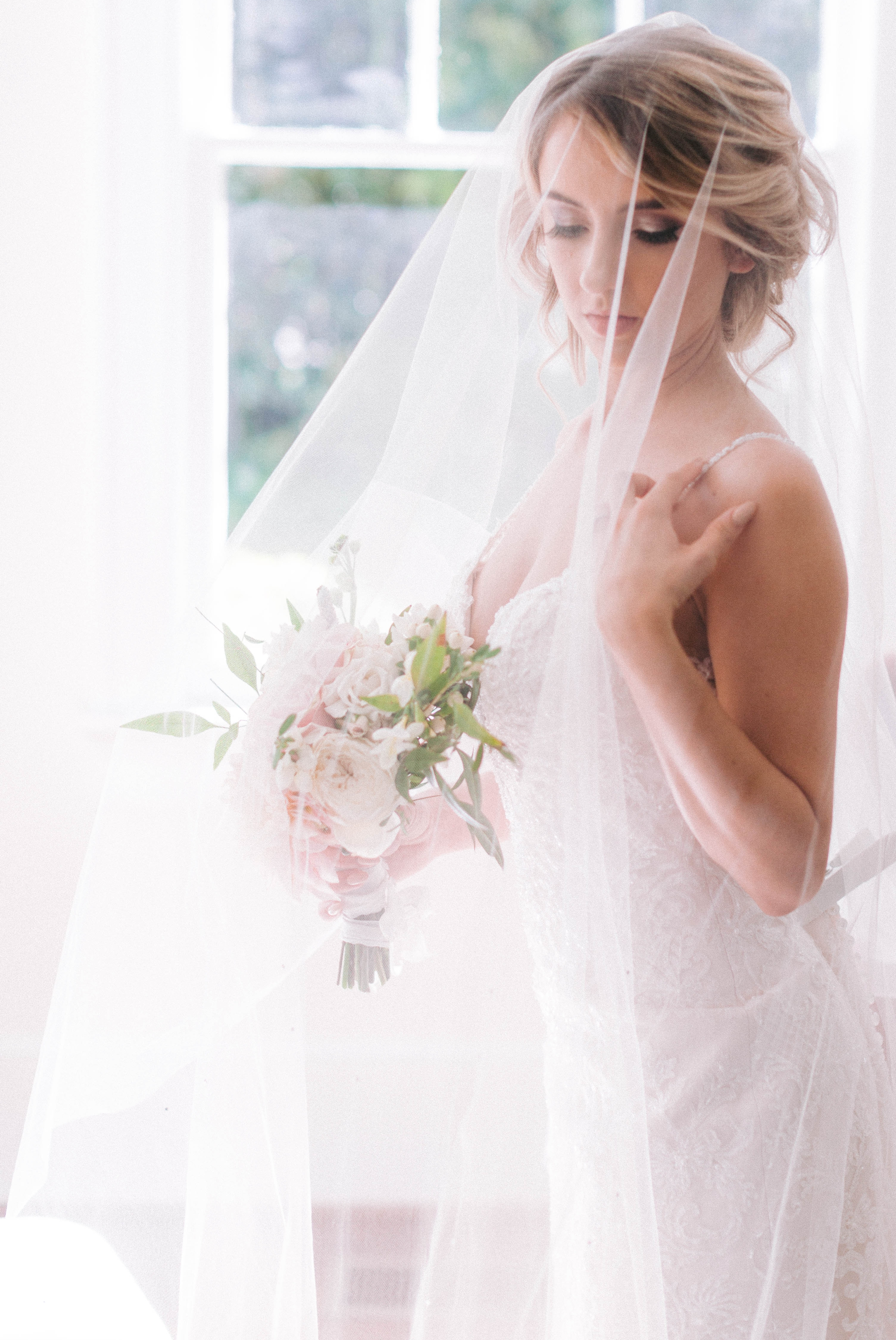 black and white Indoor Natural Light Bridal Portraits by a window with a white backdrop - classic bride with soft drop veil over her face - wedding gown by Stella York - Honolulu, Oahu, Hawaii Wedding Photographer
