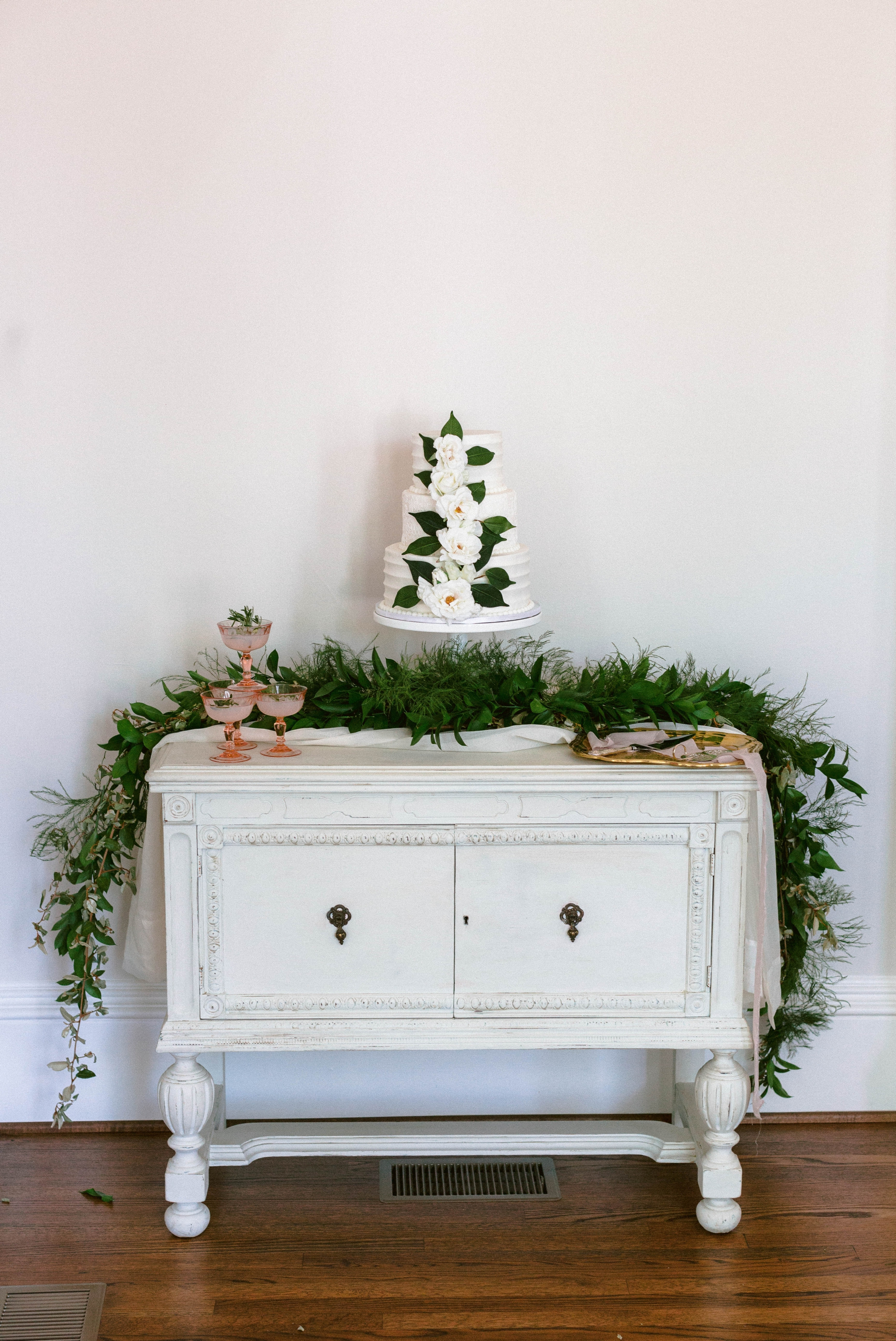 cake table on an all white antique dresser with an all white cake decorated with greenery -  luxury cake table inspiration - honolulu oahu hawaii wedding photographer - johanna dye photography