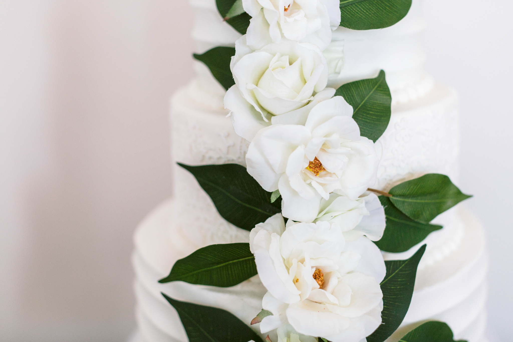 wedding cake table on an all white antique dresser with an all white cake decorated with greenery - luxury cake table inspiration - honolulu oahu hawaii wedding photographer - johanna dye photography