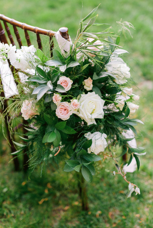 Chair Decorations with white flowers with lush greenery of charivari chairs - oahu hawaii wedding photographer