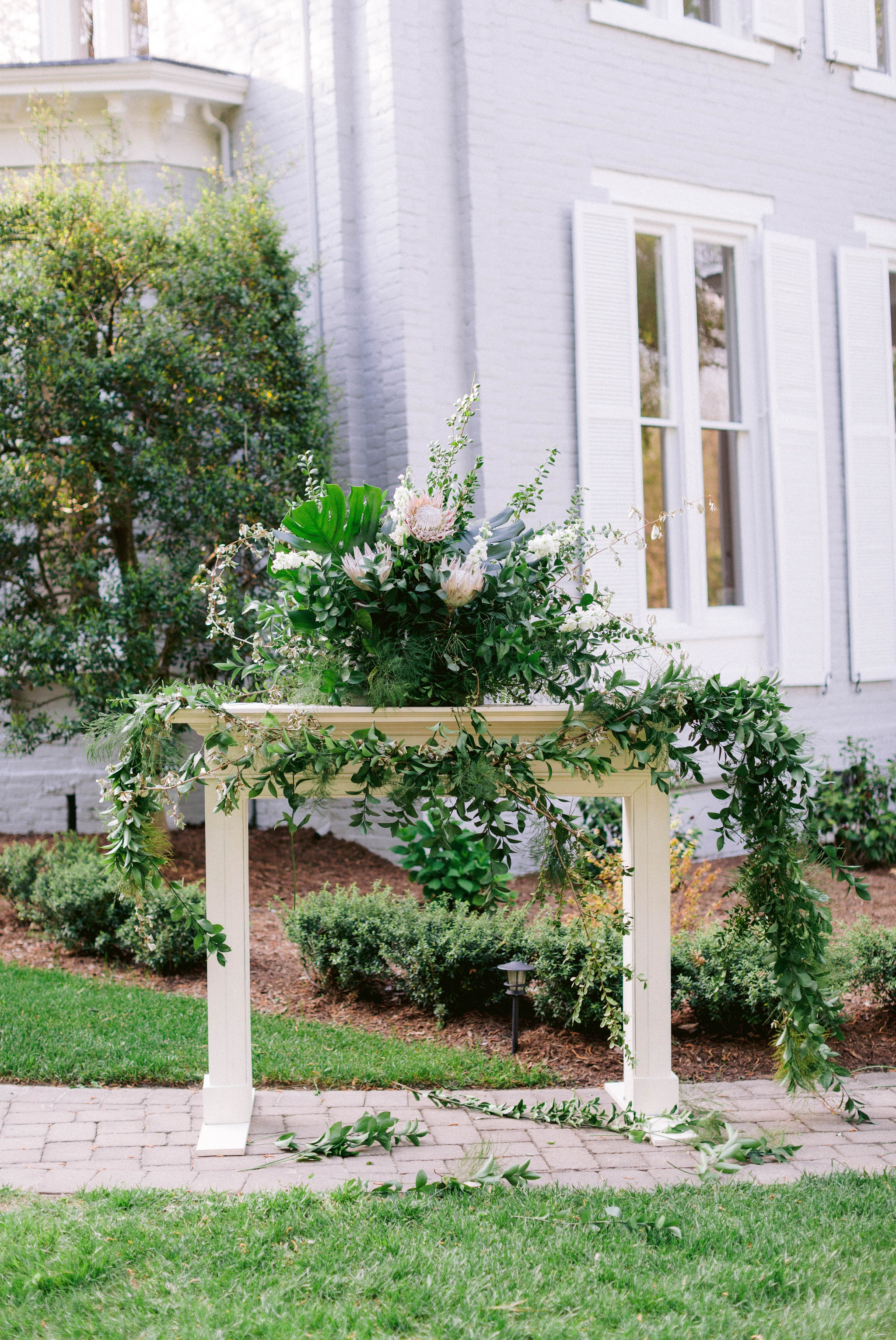 Garden Outdoor Ceremony with brown wooden chairs in front of an all white mansion - Wedding Fireplace mantel with lush green decorations - Honolulu, Oahu, Hawaii Wedding Photographer - Johanna Dye Photography