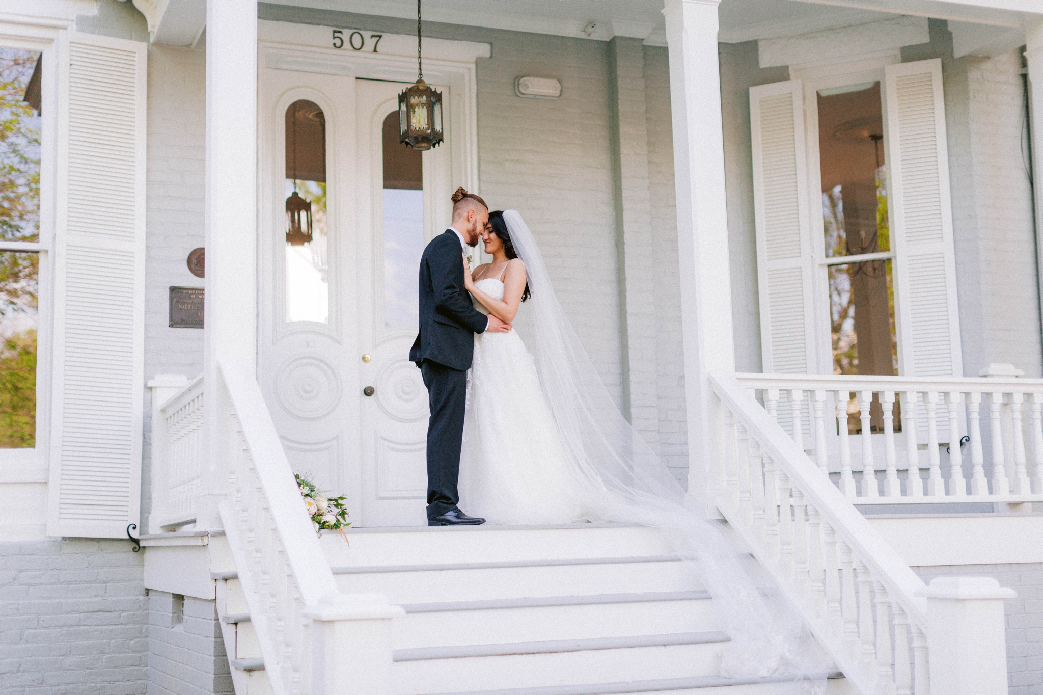 Couple Kissing - Wedding Portraits on the front porch of an all white luxury estate mansion - Bride is wearing a Aline Ballgown by Cherish by Southern Bride with a long cathedral veil - Groom is wearing a black suit by Generation Tux and has a man bun - Fine Art Honolulu Oahu Hawaii Wedding Photographer - Johanna Dye Photography - edited with for the love of film presets by jose villa