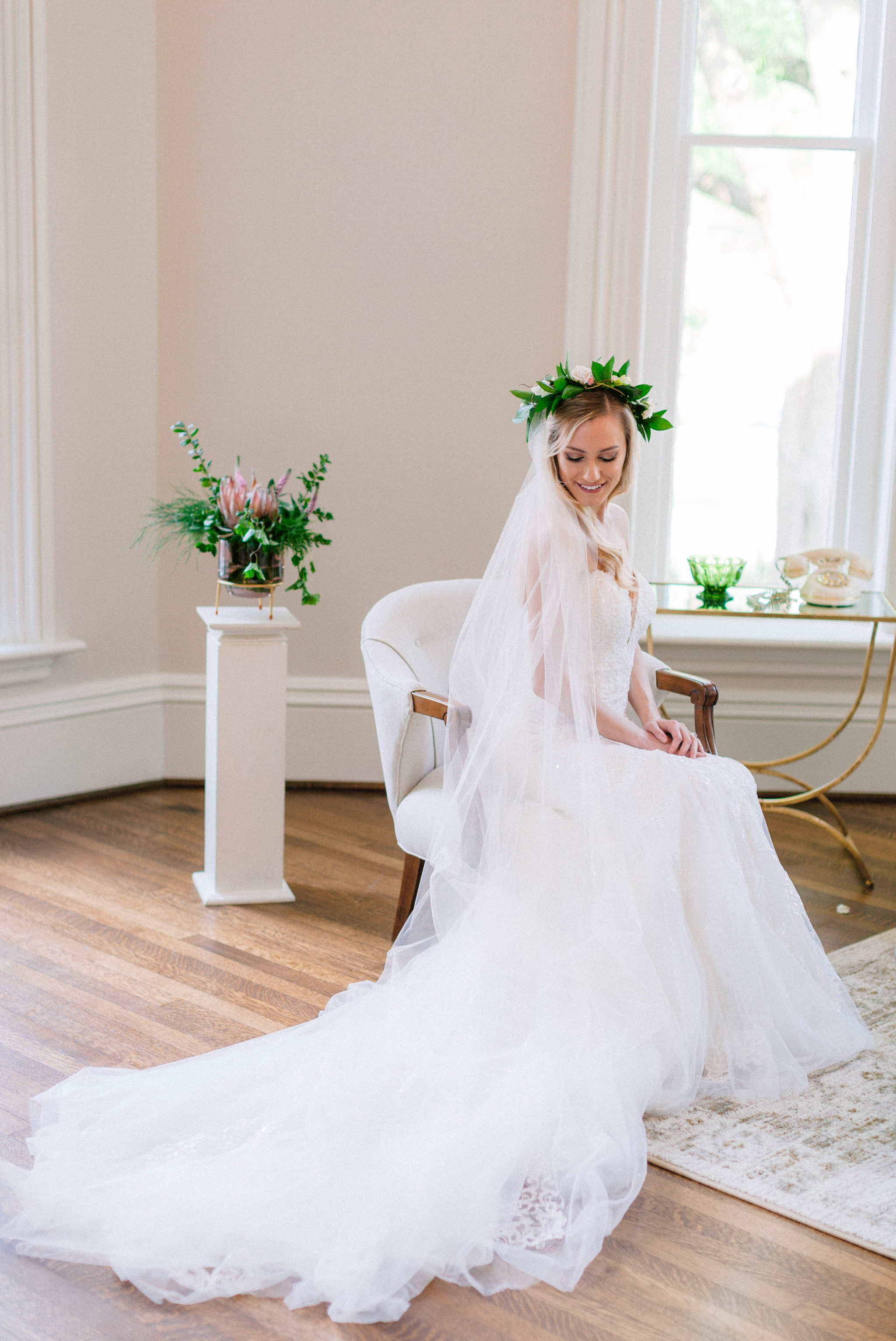 Indoor Bridal Portraits in an all white room at a luxury estate with natural light before the ceremony - Bride is wearing a Hawaiian Flower Crown and a cathedral veil in a Wedding Gown by Stella York and sitting in a chair  - Honolulu Oahu Hawaii Wedding Photographer - Johanna Dye Photography