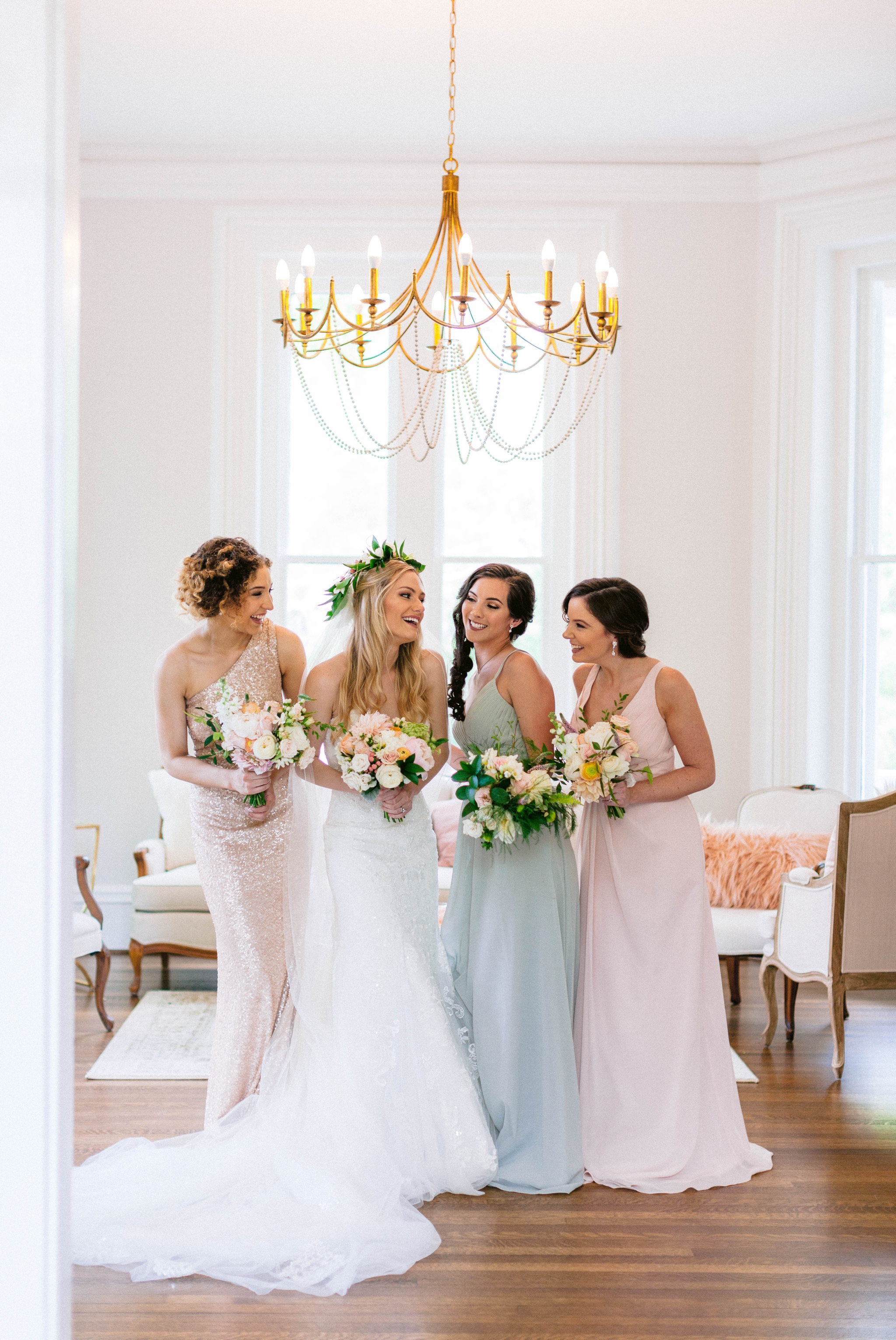 Indoor Bride + bridesmaids portraits in an all white room at a luxury estate with natural light before the ceremony - Bride is wearing a Hawaiian Flower Crown and a cathedral veil in a Wedding Gown by Stella York - Honolulu Oahu Hawaii Wedding Photographer - Johanna Dye Photography