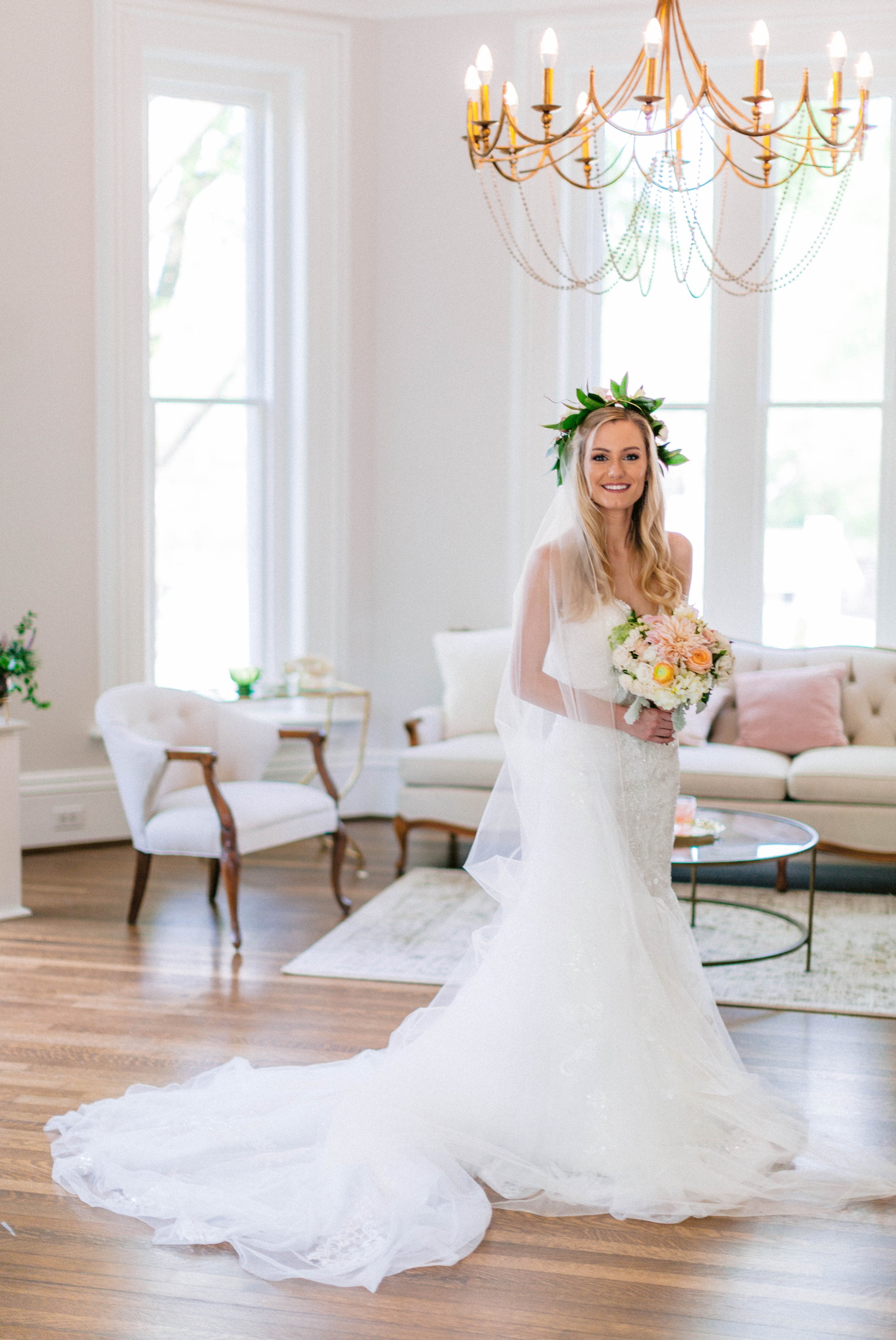 Indoor Bridal Portraits in an all white room at a luxury estate with natural light before the ceremony - Bride is wearing a Hawaiian Flower Crown and a cathedral veil in a Wedding Gown by Stella York and standing in the doorway with a golden chandelier with vintage furniture in the background - Honolulu Oahu Hawaii Wedding Photographer - Johanna Dye Photography