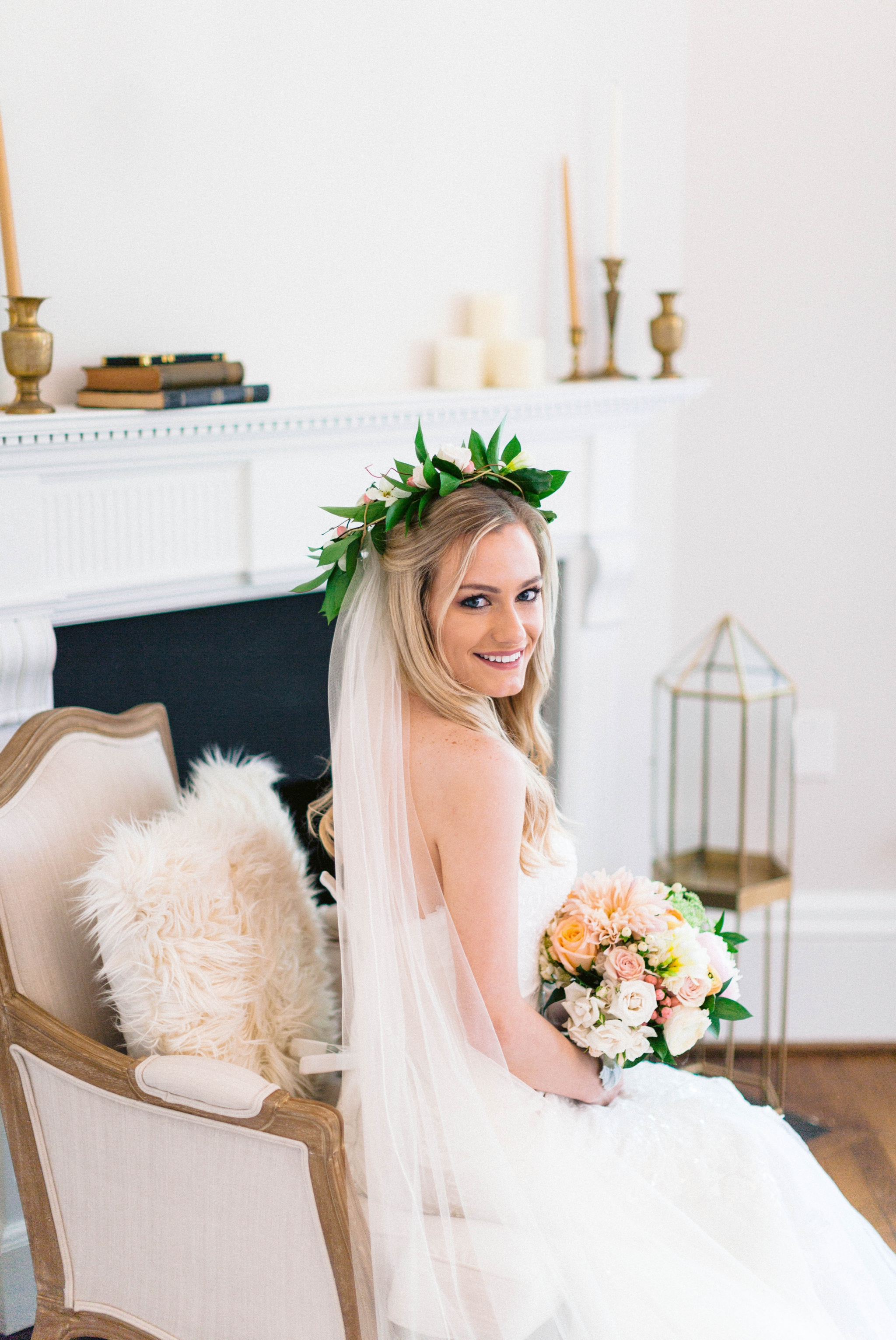 Indoor Bridal Portraits in an all white room at a luxury estate with natural light before the ceremony - Bride is wearing a Hawaiian Flower Crown and a cathedral veil in a Wedding Gown by Stella York sitting on an antique vintage chair in front of a decorated fireplace - Honolulu Oahu Hawaii Wedding Photographer - Johanna Dye Photography