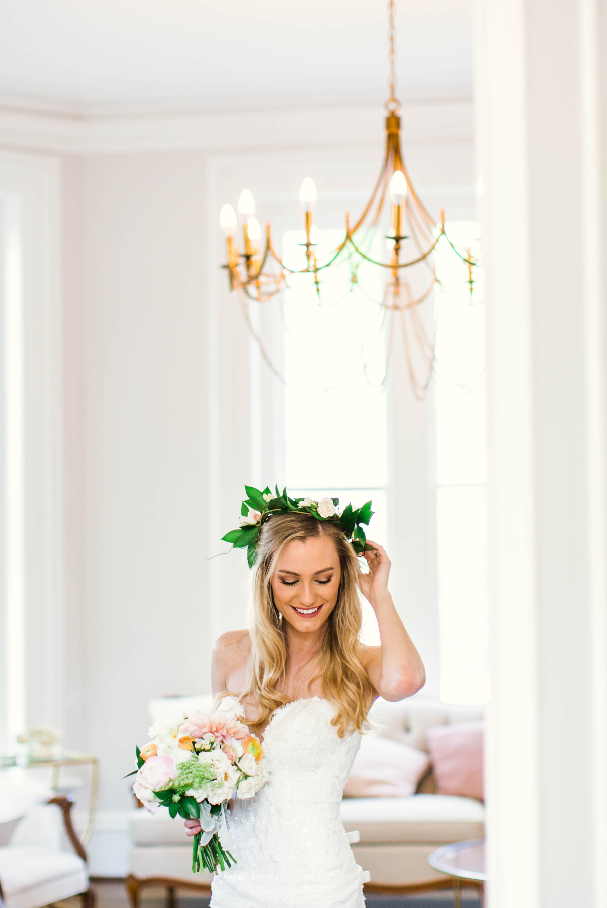 Indoor Bridal Portraits in an all white room at a luxury estate with natural light before the ceremony - Bride is wearing a Hawaiian Flower Crown in a Wedding Gown by Stella York and standing in the doorway with a golden chandelier with vintage furniture in the background - Honolulu Oahu Hawaii Wedding Photographer - Johanna Dye Photography