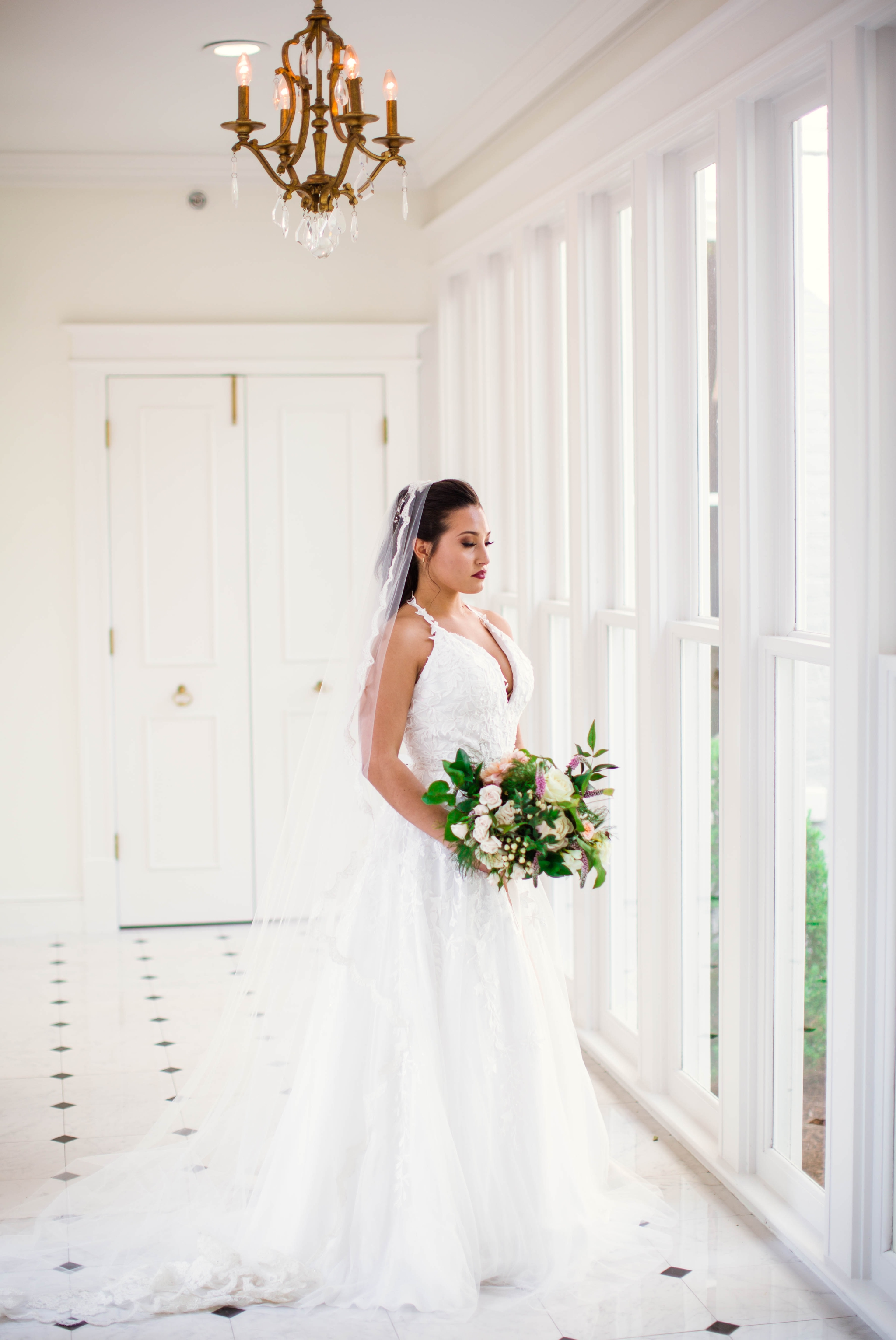 Natural light Bridal Portraits in an all white luxury estate venue with black and white floors and a golden chandelier - Bride is wearing a Wedding Dress by Sherri Hill - shot with available window light - Fine Art Wedding Photographer in Honolulu Oahu Hawaii - Johanna Dye Photography