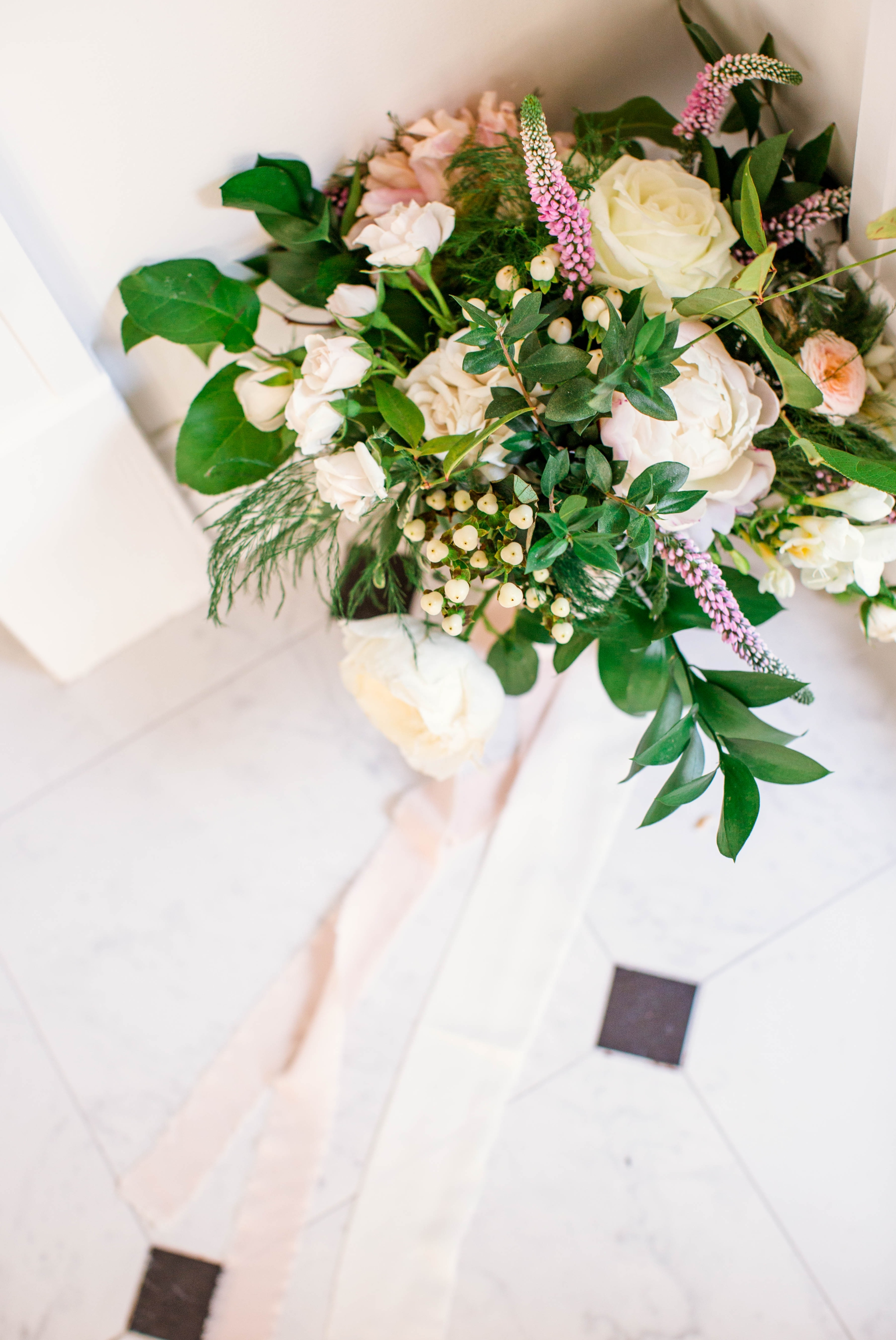 Bridal Bouquet with greenery and white flowers and paste tones on a black and white marble floor - Fine Art Wedding Photographer in Honolulu, Oahu, Hawaii - edited with the for the love of film presets by jose villa