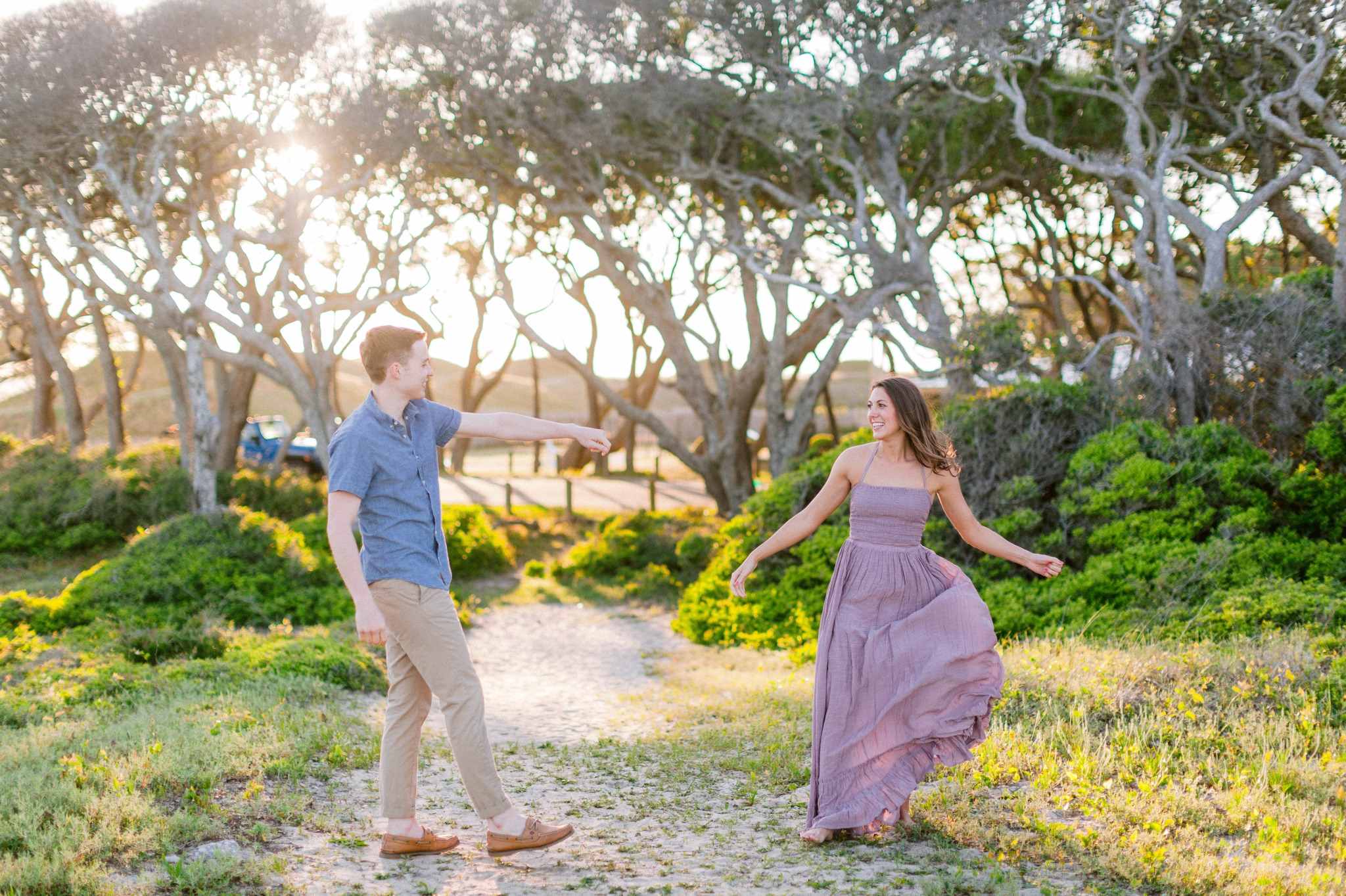 Guy dancing with girl in front of live oak trees with the sunset behind them - Woman is in a flowy pastel maxi dress - outdoor golden light session - engagement photographer in honolulu, oahu, hawaii - johanna dye photography
