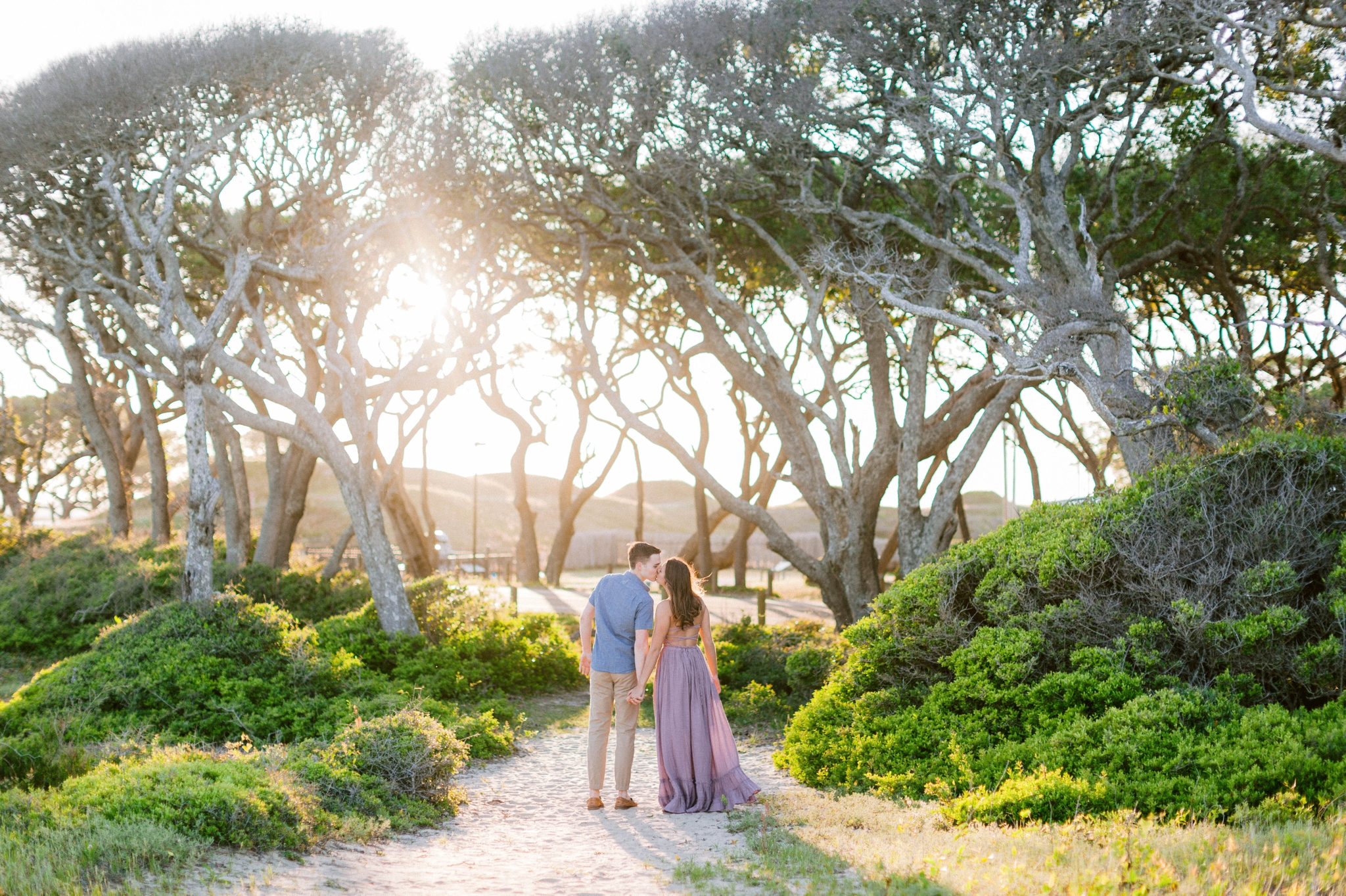 a couple walking towards the sun in front of live oak trees with the sunset behind them - Woman is in a flowy pastel maxi dress - unposed and candid outdoor golden light session - engagement photographer in honolulu, oahu, hawaii - johanna dye