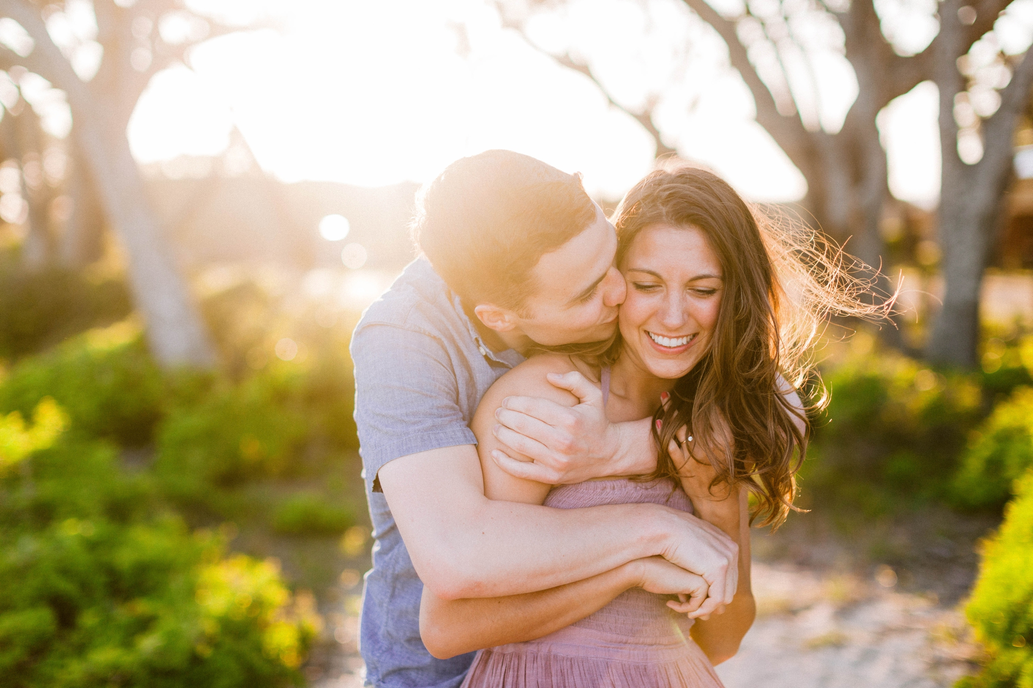 Guy kissing a girl in front of live oak trees with the sunset behind them - Woman is in a flowy pastel maxi dress - outdoor golden light session - engagement photographer in honolulu, oahu, hawaii - johanna dye photography