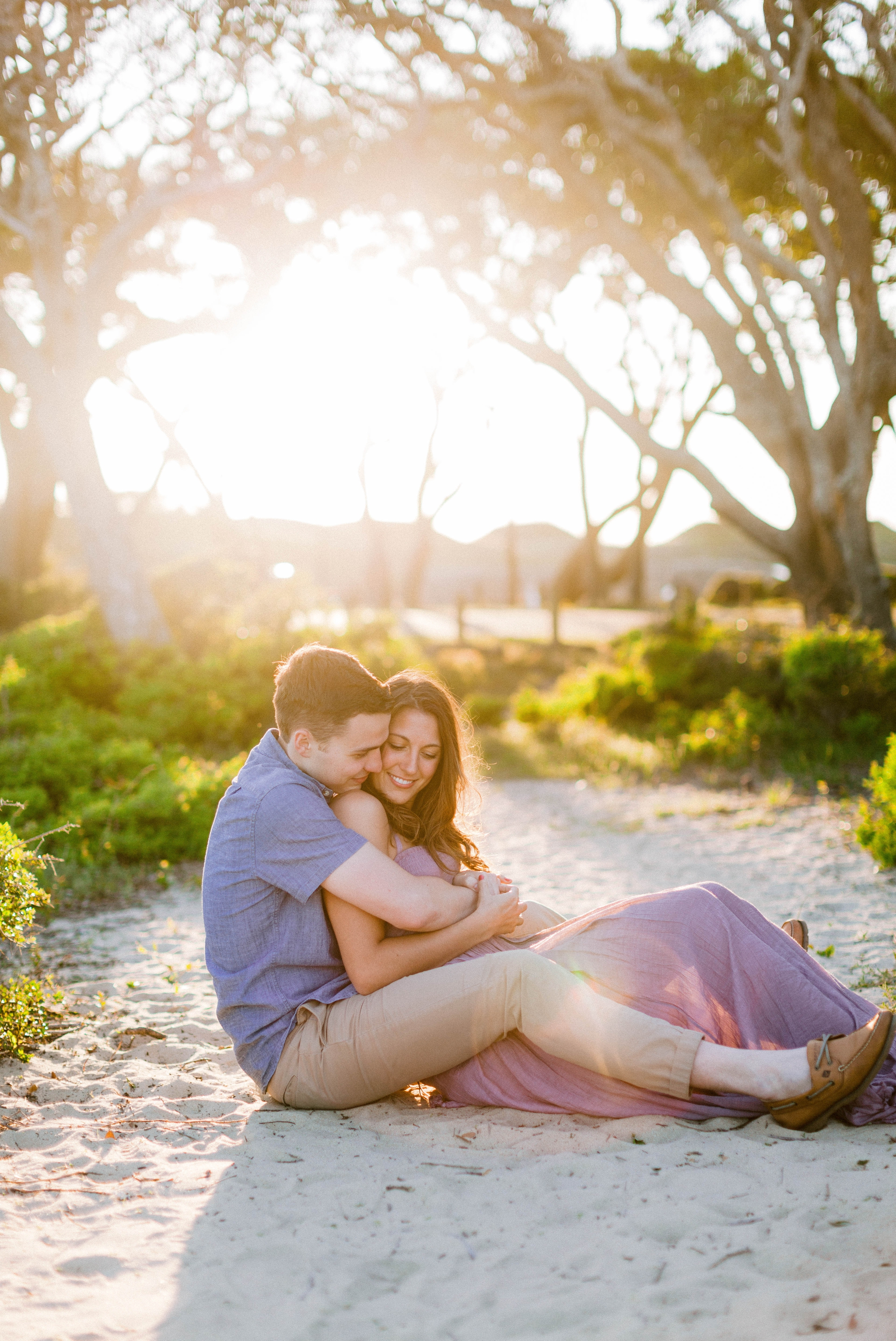 couple giggeling on the beach in front of live oak trees with the sunset behind them - Woman is in a flowy pastel maxi dress - outdoor golden light session - engagement photographer in honolulu, oahu, hawaii - johanna dye photography