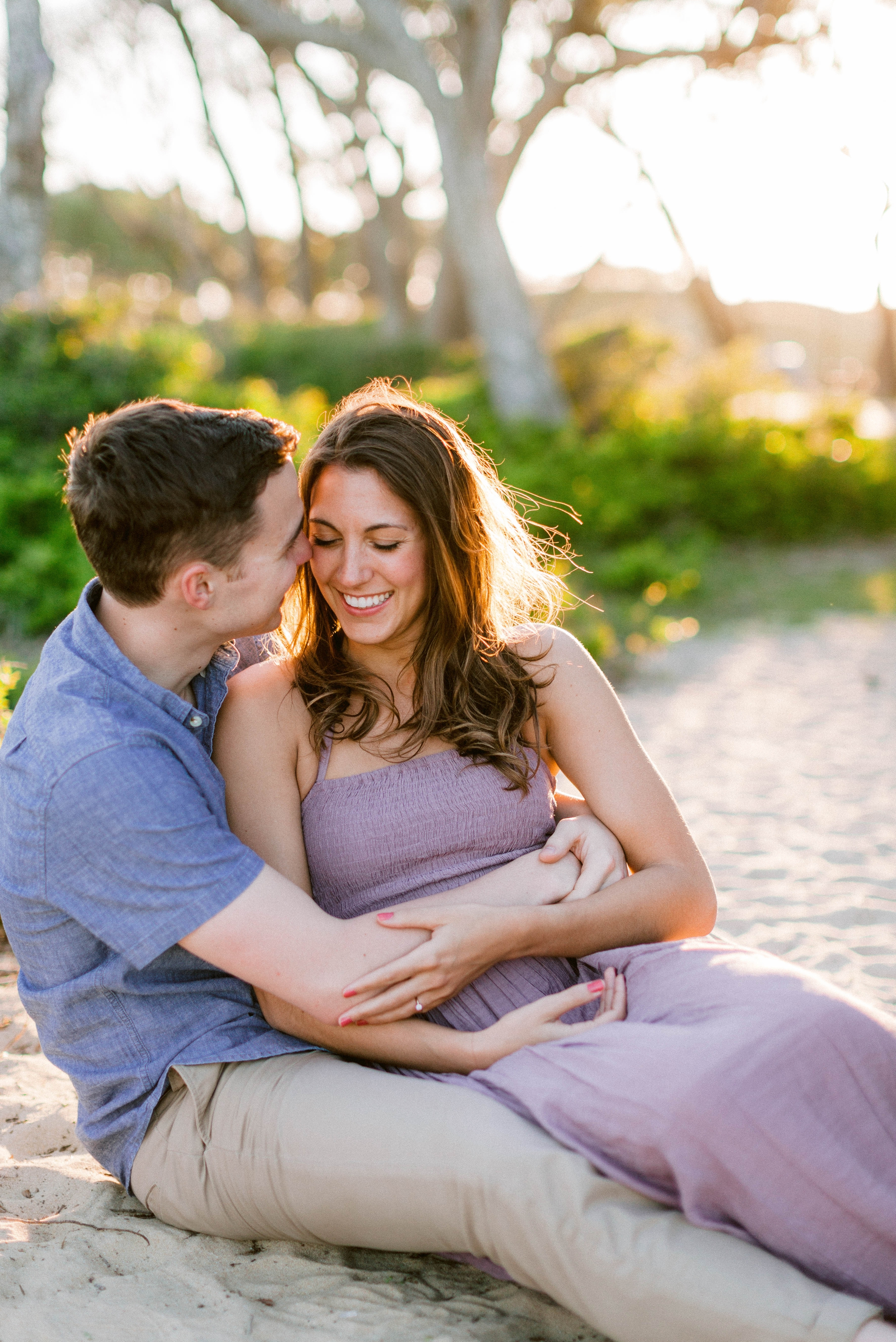 couple cuddeling on the beach in front of live oak trees with the sunset behind them - Woman is in a flowy pastel maxi dress - outdoor golden light session - engagement photographer in honolulu, oahu, hawaii - johanna dye photography