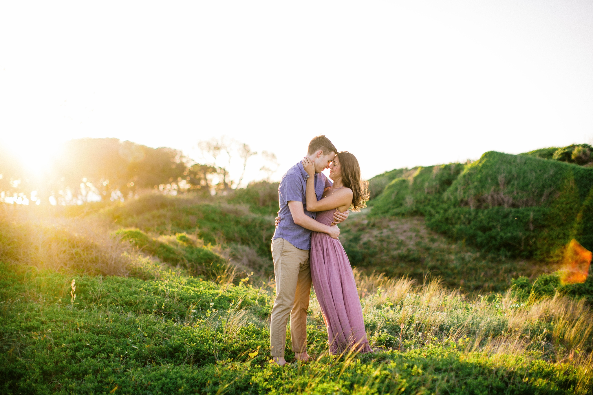 couple kissing in front of lush green dunes and hills with the sunset behind them - Woman is in a flowy pastel maxi dress - outdoor golden light session - engagement photographer in honolulu, oahu, hawaii - johanna dye photography