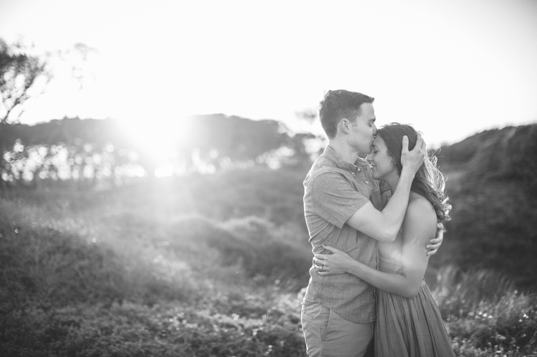 couple looking at each other while his hand is in her hair wile he is kissing her on the forehead- in front of lush green dunes and hills with the sunset behind them - Woman is in a flowy pastel maxi dress - outdoor golden light session - engagement photographer in honolulu, oahu, hawaii - johanna dye photography