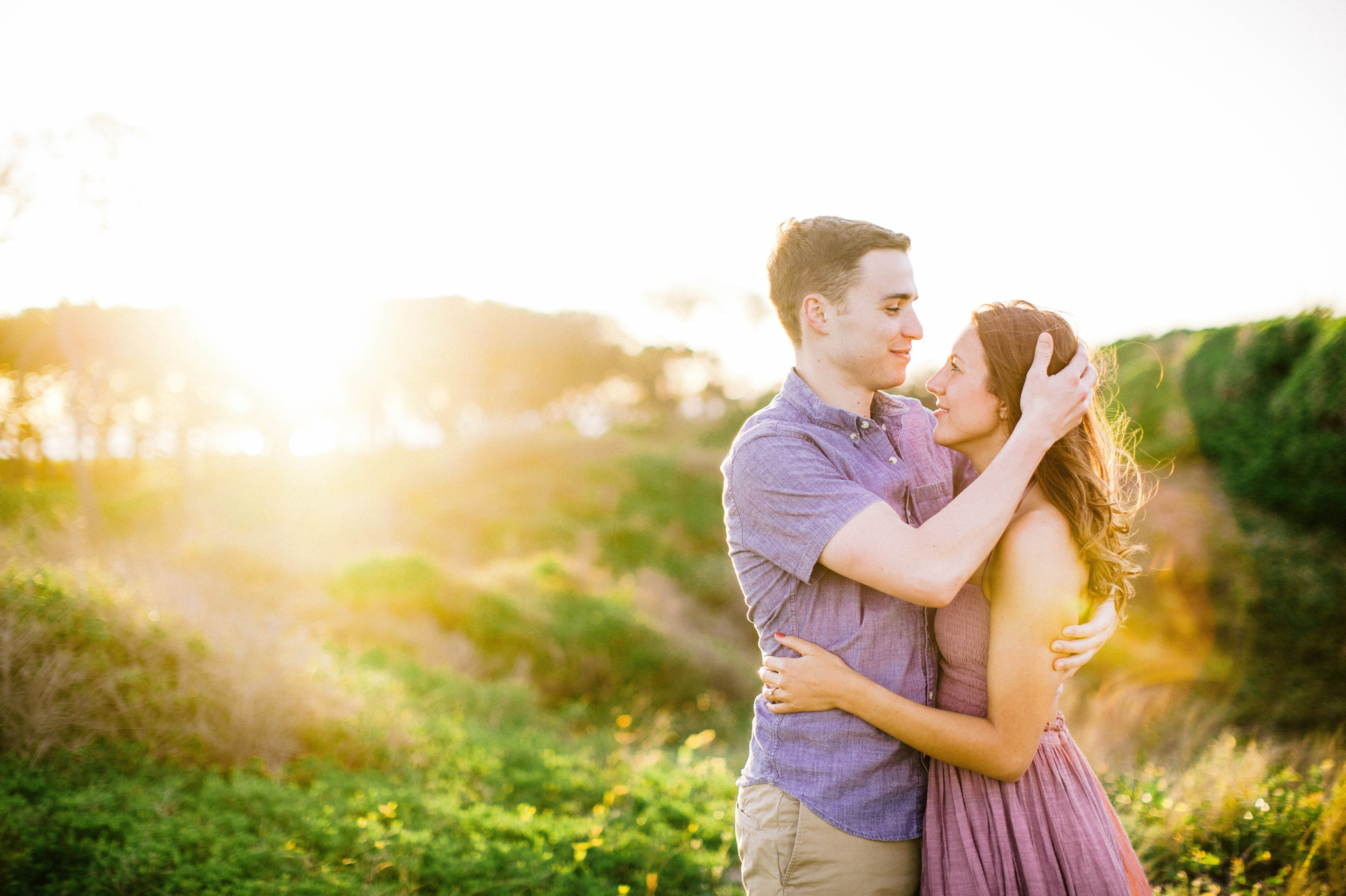couple looking at each other while his hand is in her hair - in front of lush green dunes and hills with the sunset behind them - Woman is in a flowy pastel maxi dress - outdoor golden light session - engagement photographer in honolulu, oahu, hawaii - johanna dye photography