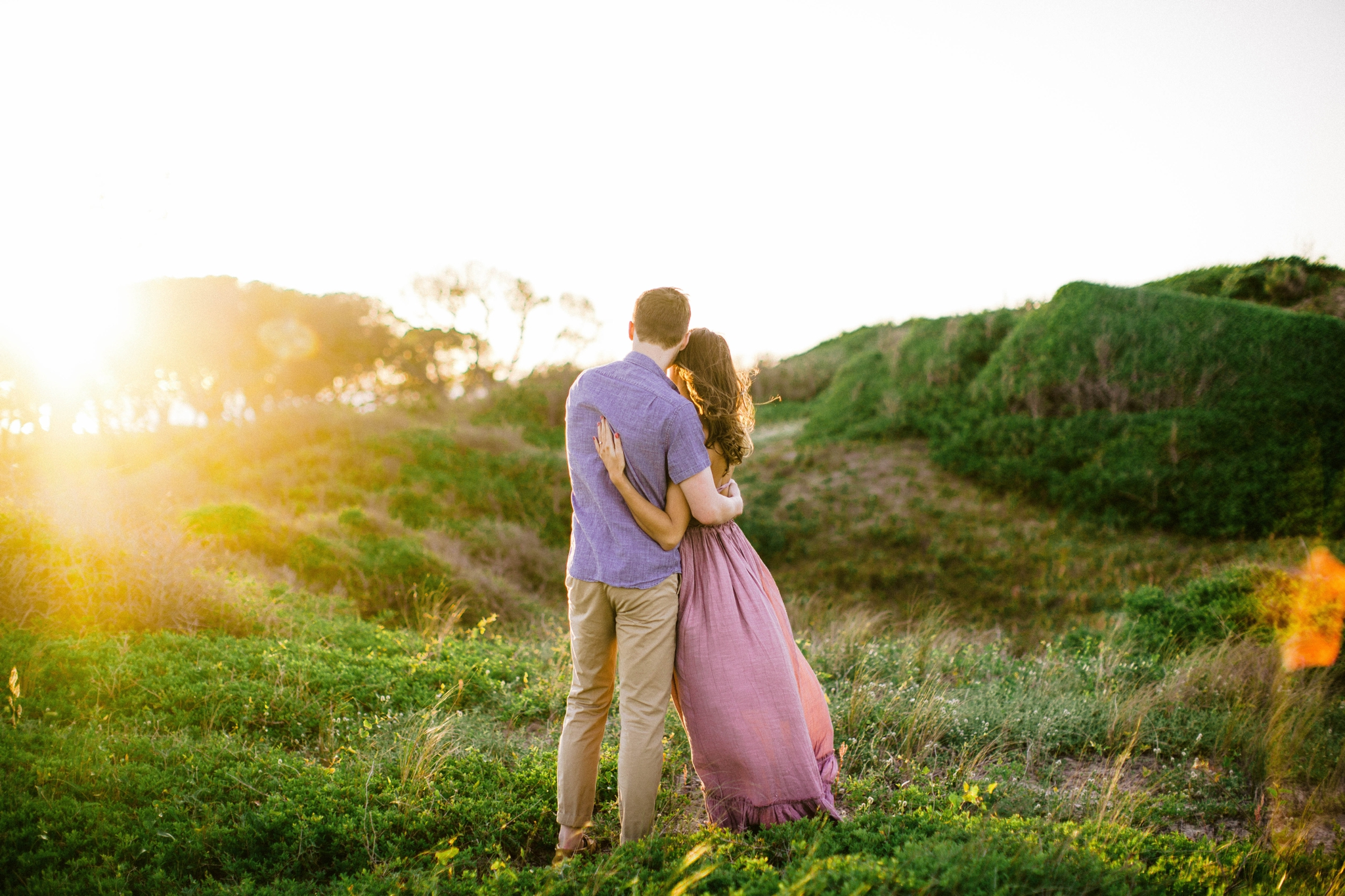 couple looking at the sunset  - in front of lush green dunes and hills with the sunset behind them - Woman is in a flowy pastel maxi dress - candid and unposed outdoor golden light session - engagement photographer in honolulu, oahu, hawaii - johanna dye photography