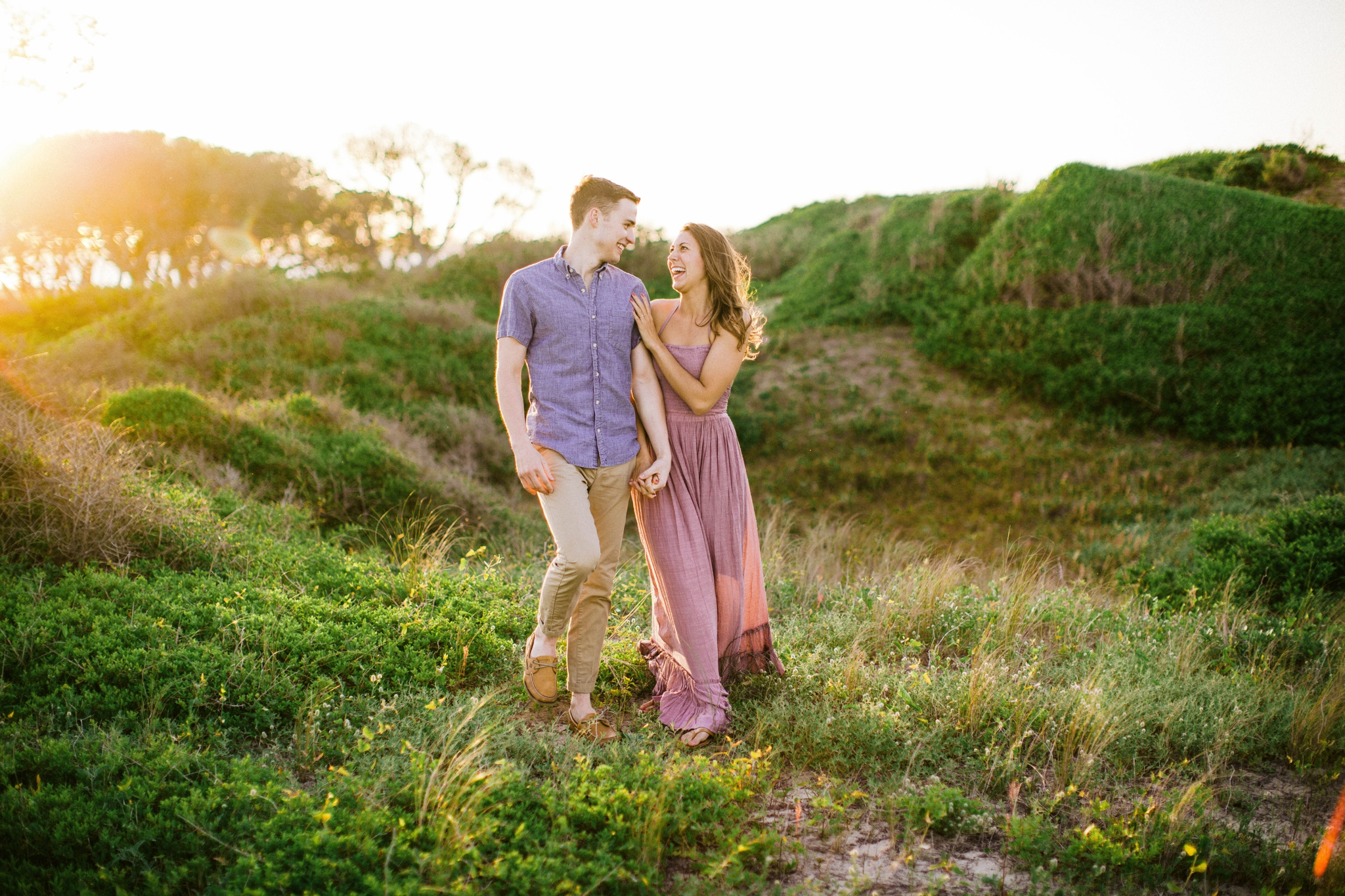 couple walking and laughing - in front of lush green dunes and hills with the sunset behind them - Woman is in a flowy pastel maxi dress - candid and unposed outdoor golden light session - engagement photographer in honolulu, oahu, hawaii - johanna dye photography