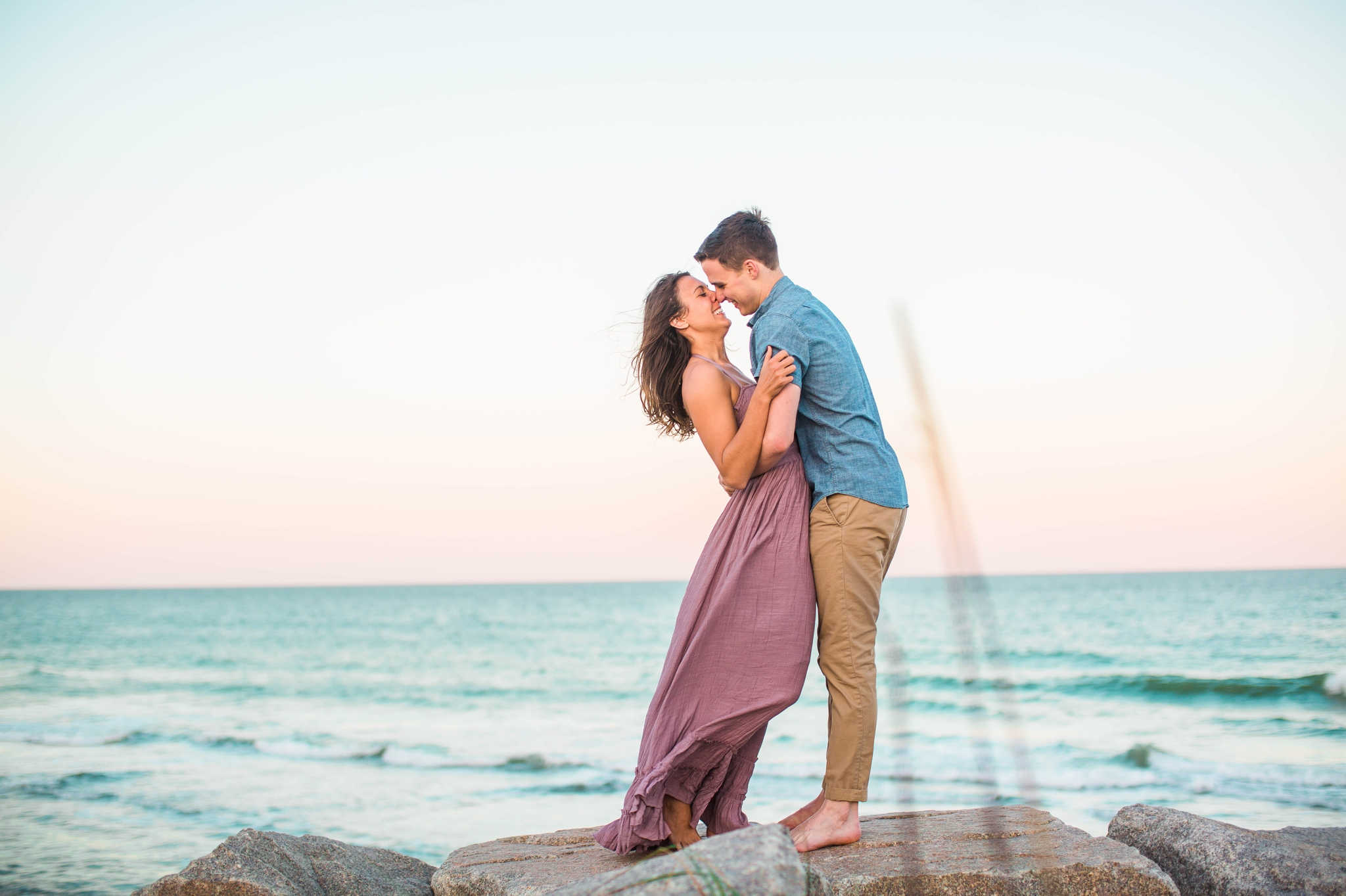 couple on the cliffs kissing - Woman is in a flowy pastel maxi dress - candid and unposed golden light session - beach engagement photographer in honolulu, oahu, hawaii - johanna dye photography