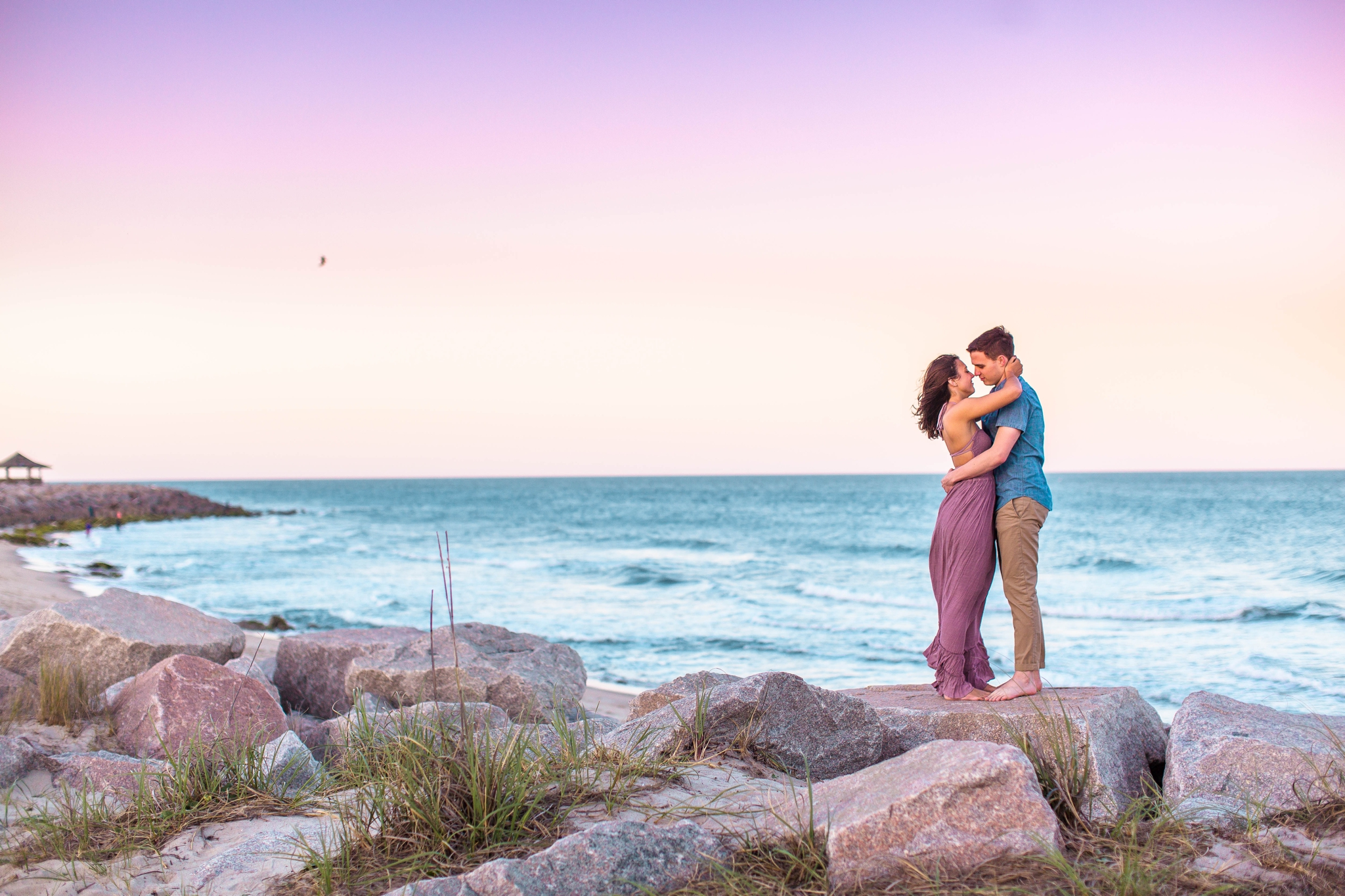 Couple kissing on the cliffs at sunset - Woman is in a flowy pastel maxi dress - candid and unposed golden light session - beach engagement photographer in honolulu, oahu, hawaii - johanna dye photography