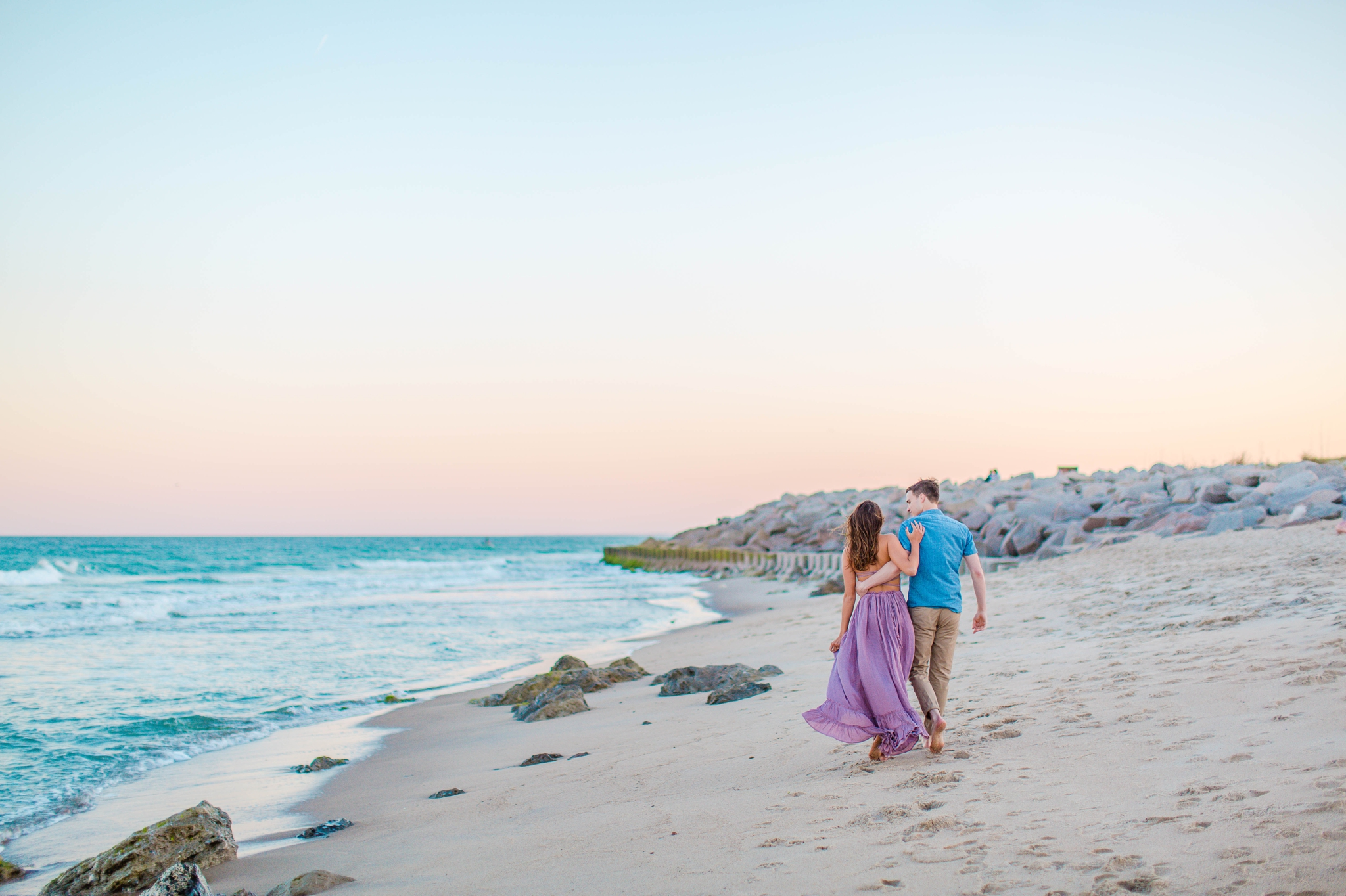 couple on the beach walking and laughing - - Woman is in a flowy pastel maxi dress - candid and unposed golden light session - beach engagement photographer in honolulu, oahu, hawaii - johanna dye photography
