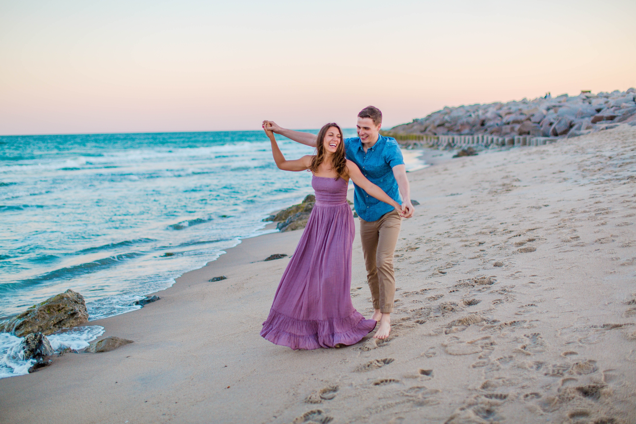couple playing on the beach - Woman is in a flowy pastel maxi dress - candid and unposed golden light session - beach engagement photographer in honolulu, oahu, hawaii - johanna dye photography