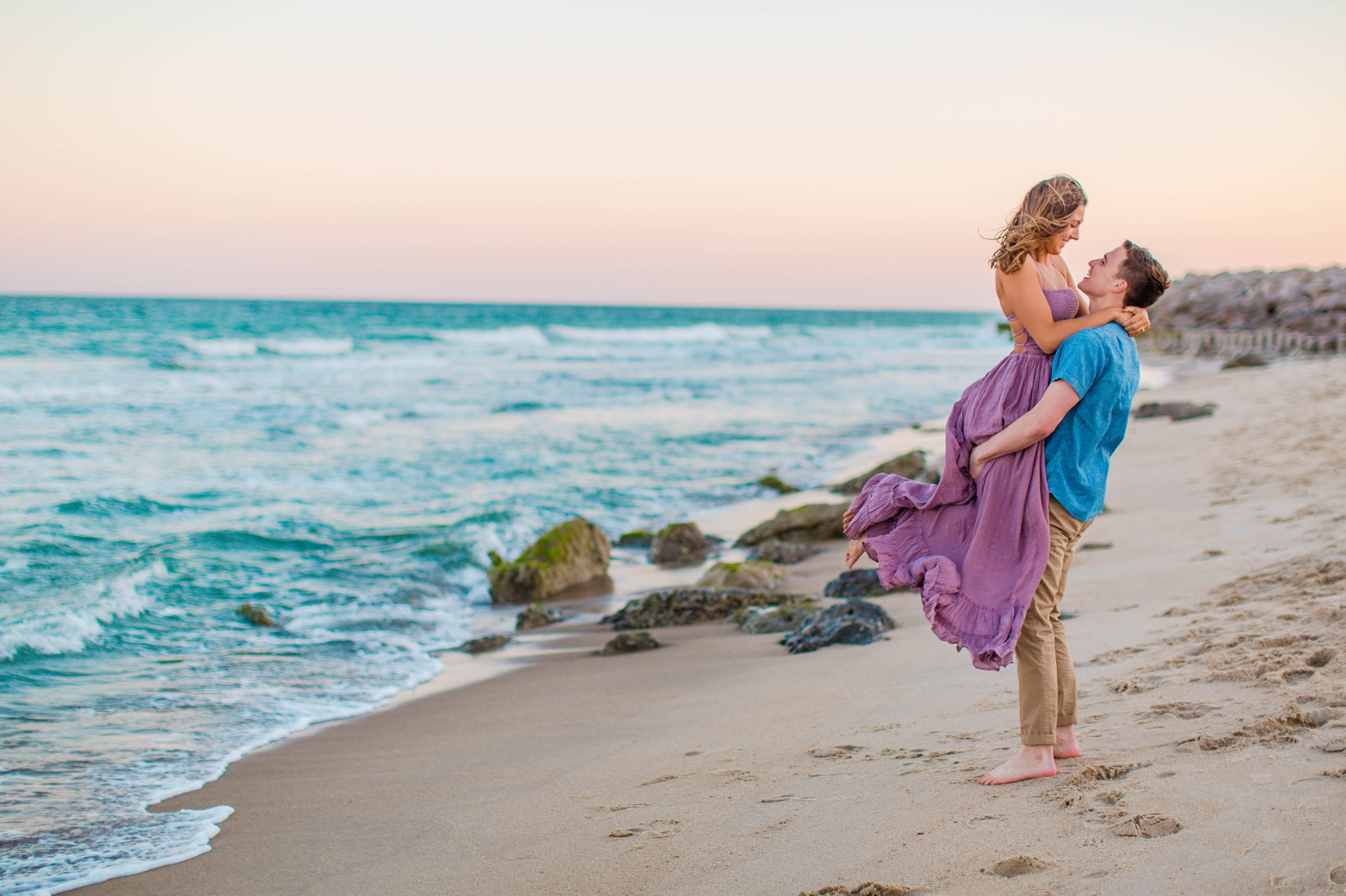 fiance picking up his girl - - Woman is in a flowy pastel maxi dress - candid and unposed golden light session - beach engagement photographer in honolulu, oahu, hawaii - johanna dye photography