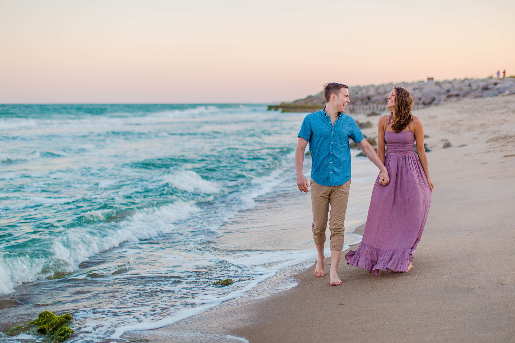 GUY AND his fiance walking in the water - - Woman is in a flowy pastel maxi dress - candid and unposed golden light session - beach engagement photographer in honolulu, oahu, hawaii - johanna dye photography