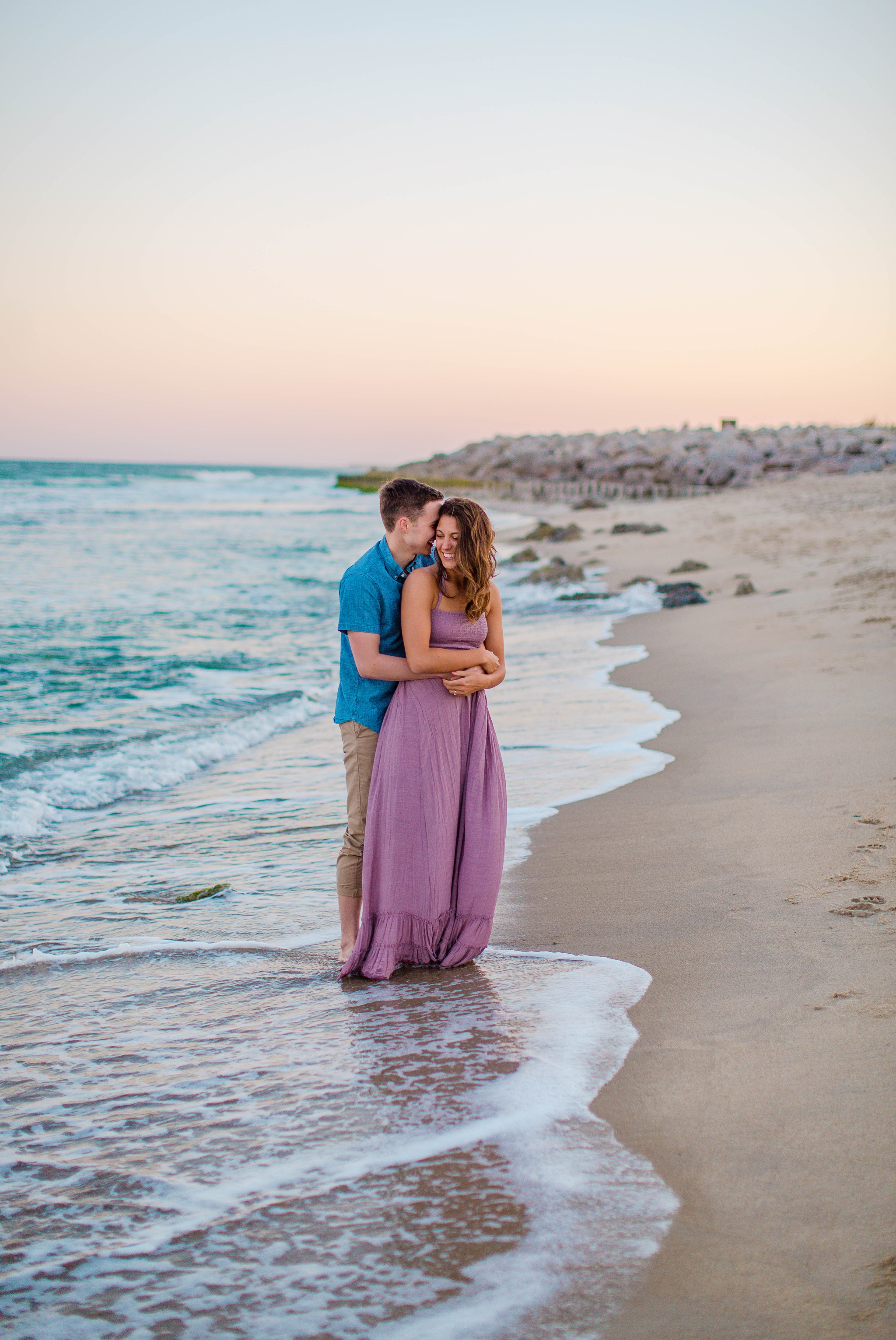 man and woman standing in the water and cuddling - - Woman is in a flowy pastel maxi dress - candid and unposed golden light session - beach engagement photographer in honolulu, oahu, hawaii - johanna dye photography
